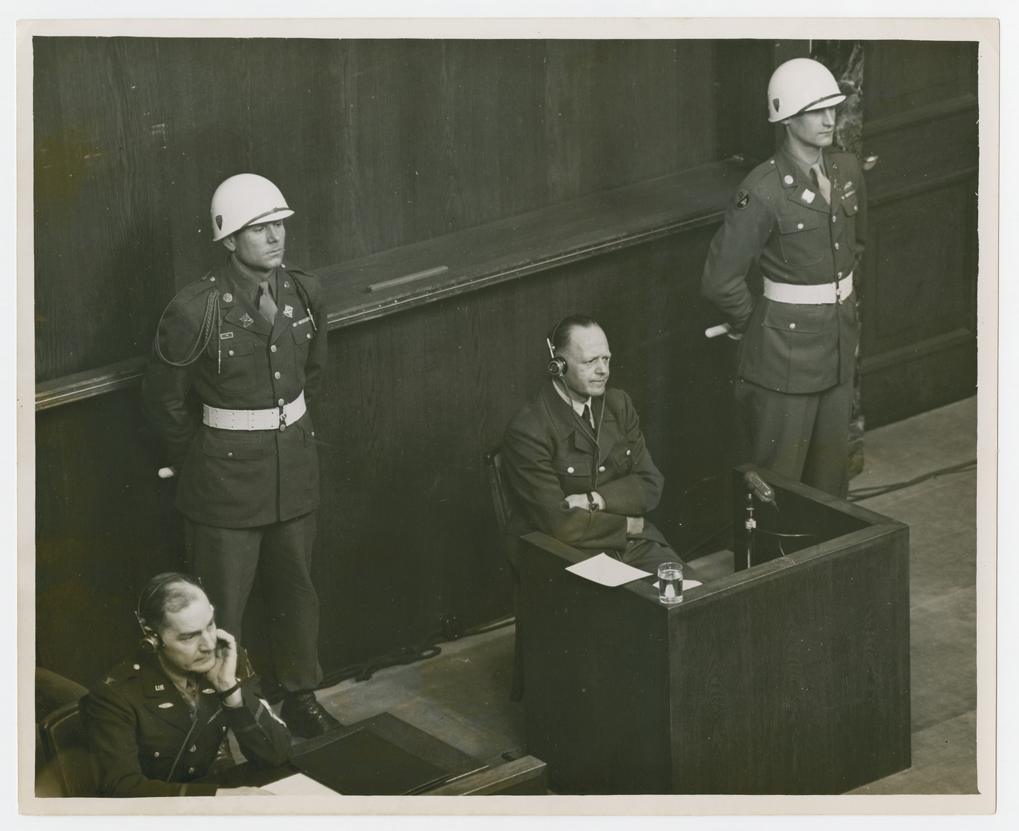 Erhard Milch sits at the defendants block flanked by American military police during his trial in Nuremberg.