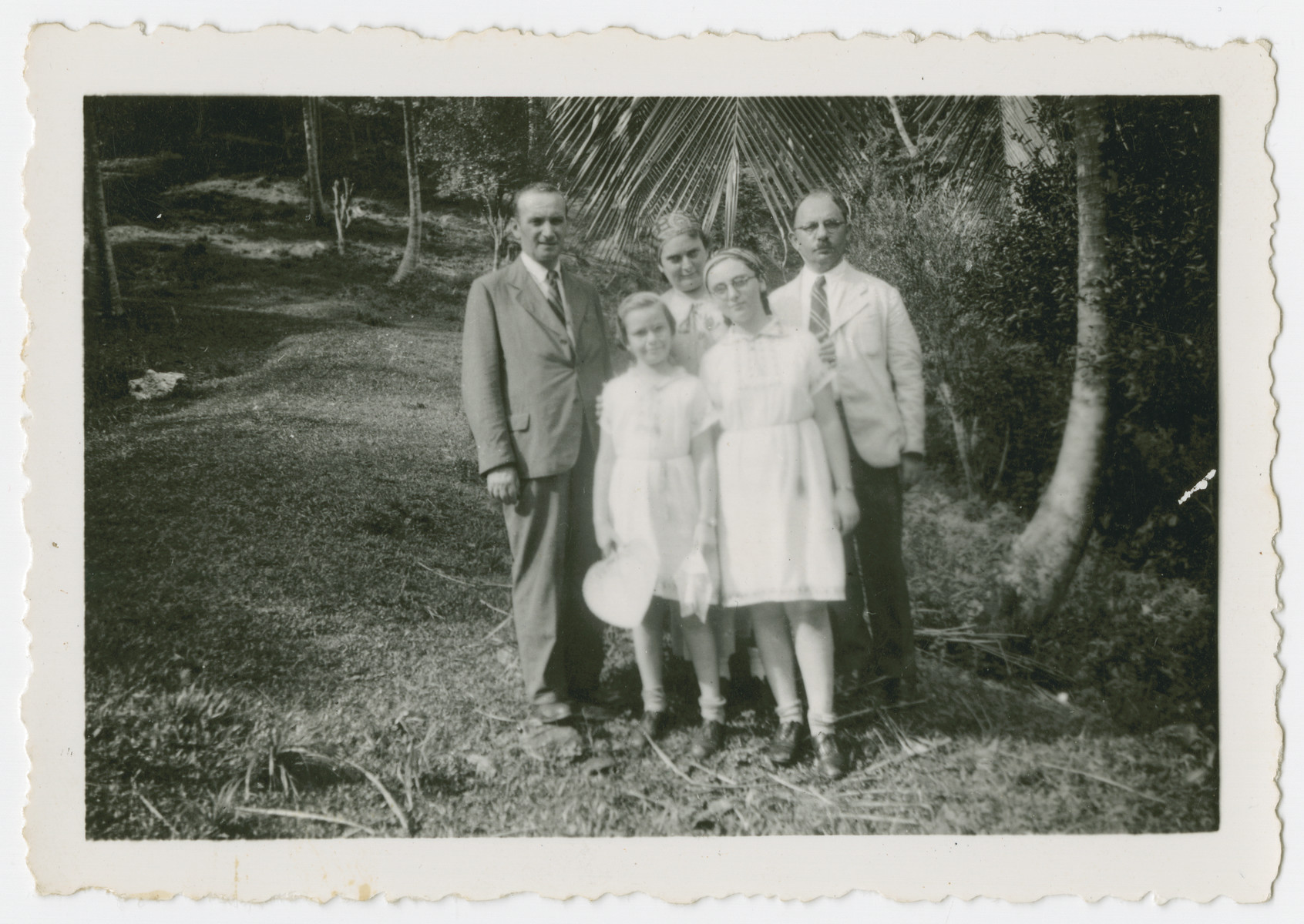 The Tauscher family poses outside in Trinidad where they arrived as refugees.  From left to right are [possibly Erich], Alice Tauscher, Bertha Tauscher, Trudie Tauscher and Victor Stecher.