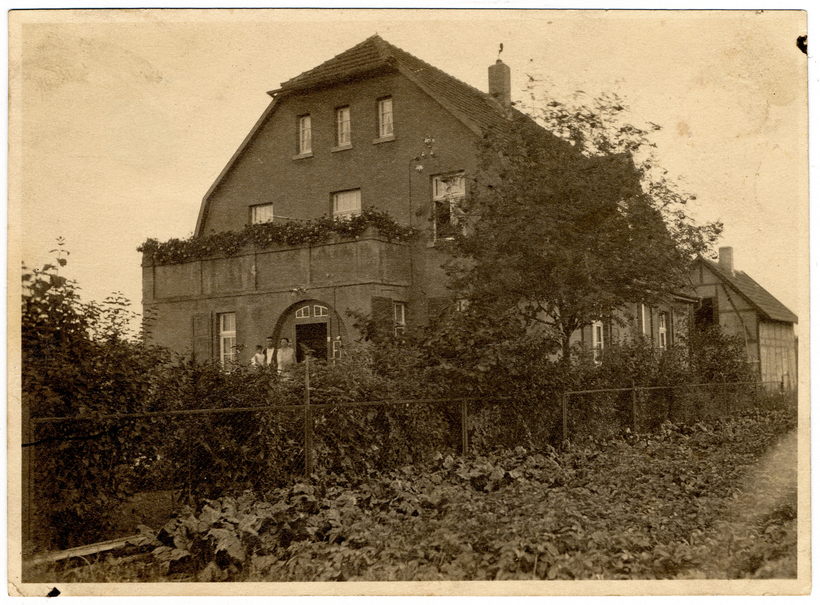 View of the Wertheim home in Brakel, Germany.  Erich, Margarete and Martin Wertheim are standing by the entrance.