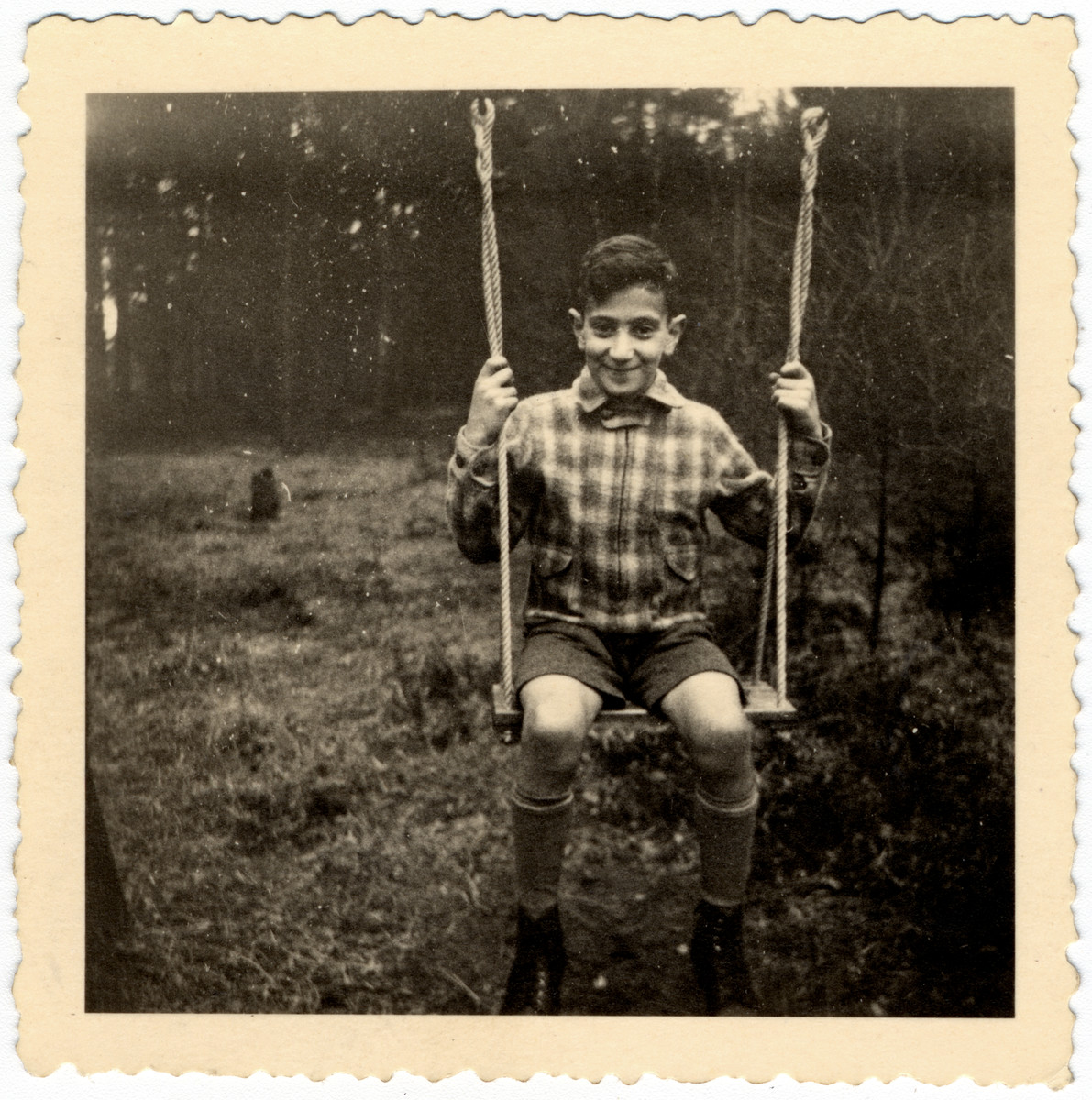 Martin Wertheim sits on a swing in a garden in Bissendorf shortly before he left on the Kindertransport.