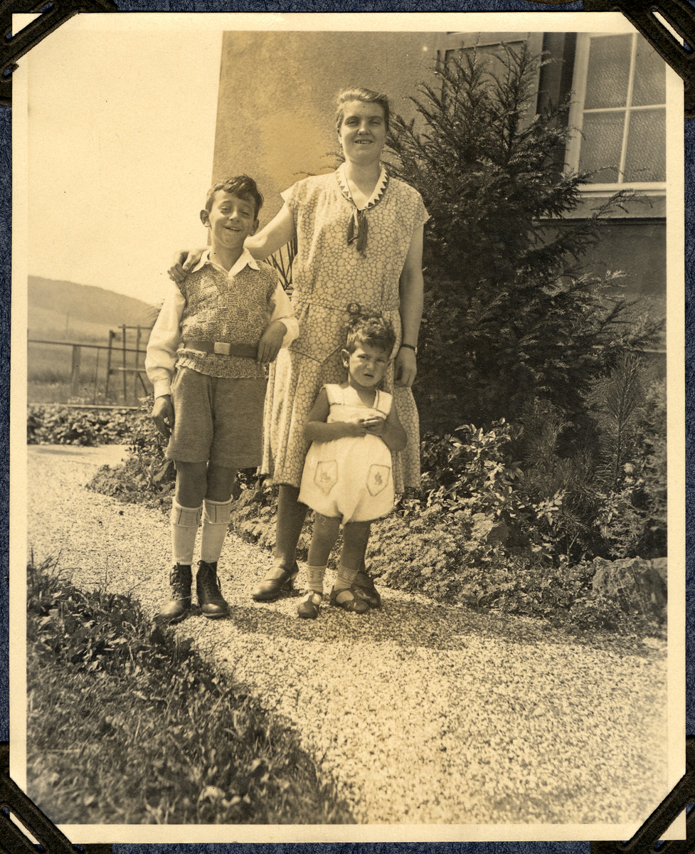 Martin and Ernst Wertheim pose outside their family home with their housekeeper.