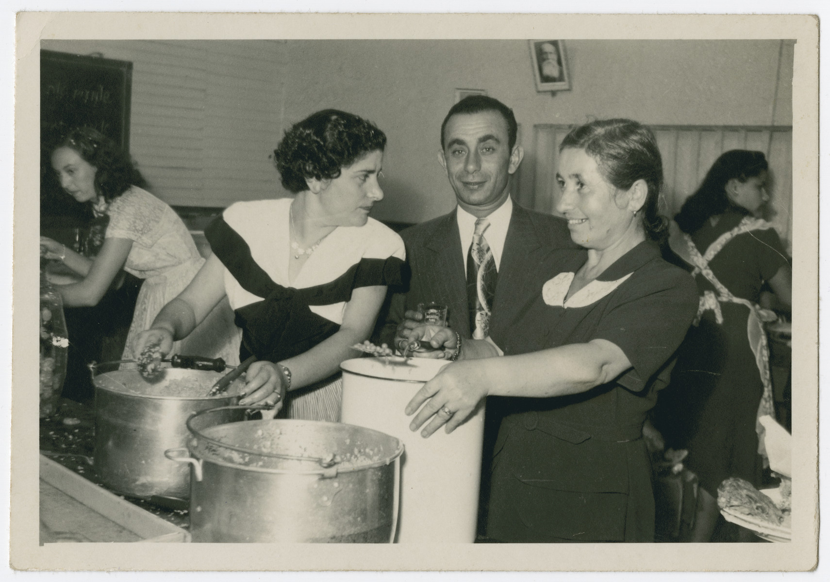 "Jewish immigrants to Costa Rica serve food at a wedding of survivors from Zelechow.  The sign on the wall reads ""speak Yiddish"".  Pictured are Eva Goldberg, Sara Ickowicz, and Sara Goldberg."