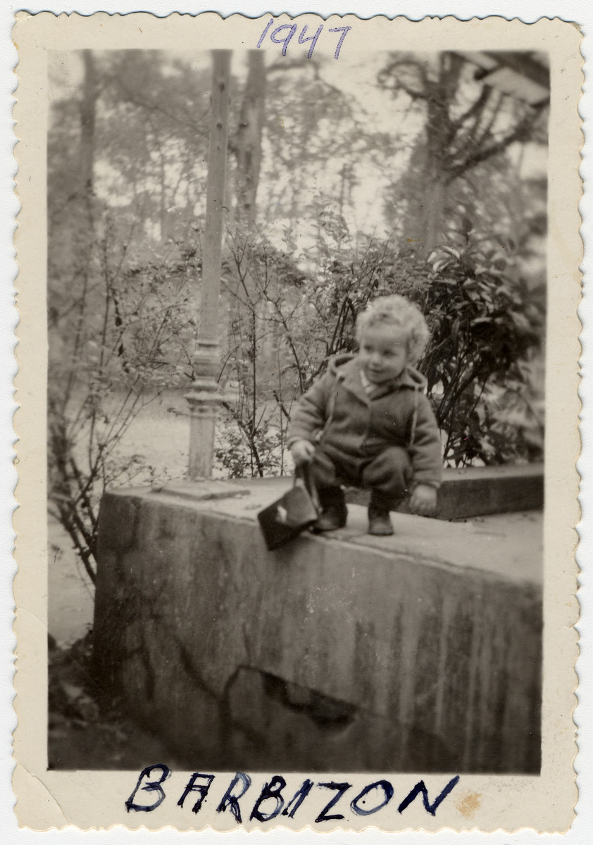 Two-year-old Leslie Rosenthal climbs on a ledge outside the Barbizon children's home near Paris.