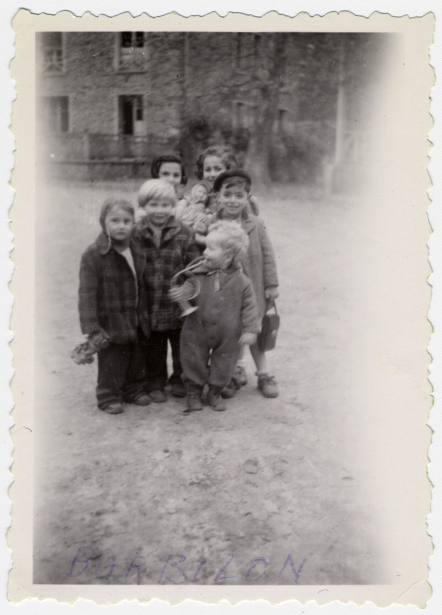 Group portrait of young children, many holding toys, at the Barbizon children's home near Paris.