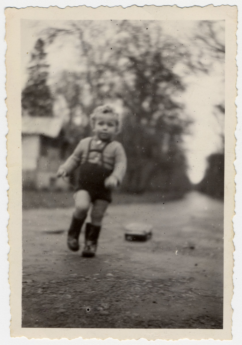 Leslie Rosenthal runs outside the Barbizon children's home wearing rubber boots sent to him from Canada.