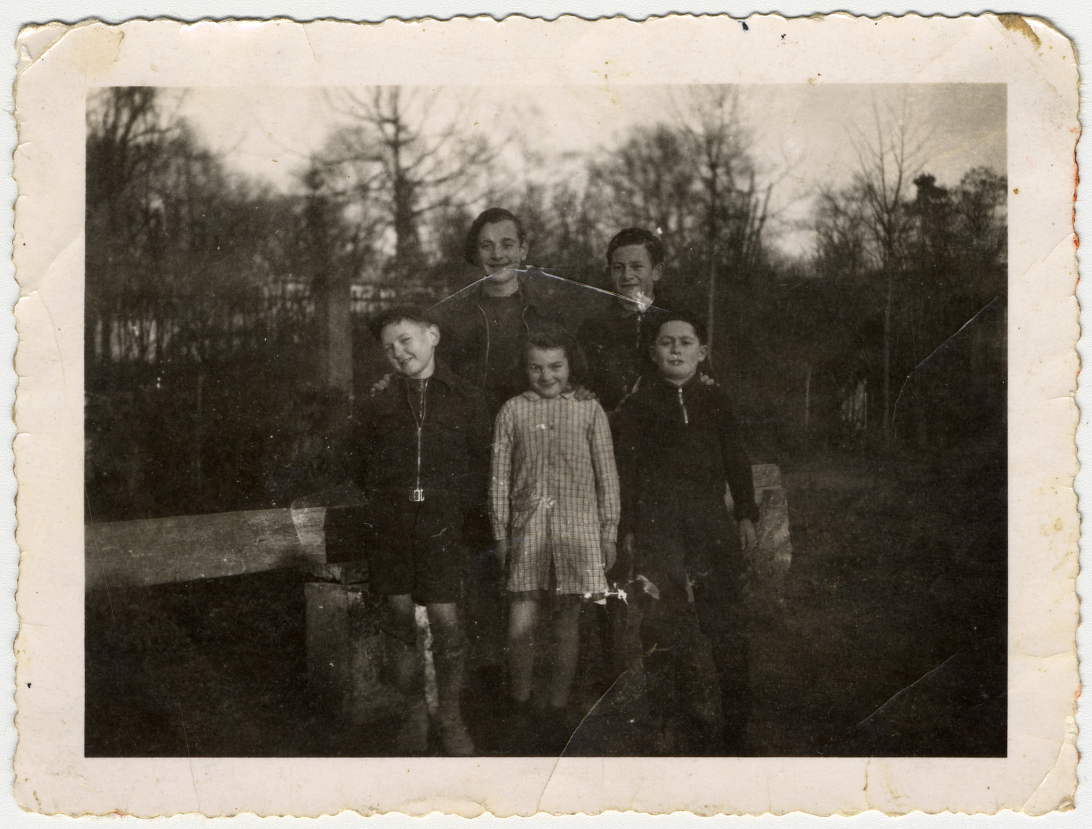 Group portrait of two sets of siblings standing on the grounds of the Chateau des Morelles children's home.  Pictured in the front row (left to right) are Simon Belk, Suzanne Belk and Markus Horowitz.  Second row: David Belk and Raphael Horowitz.