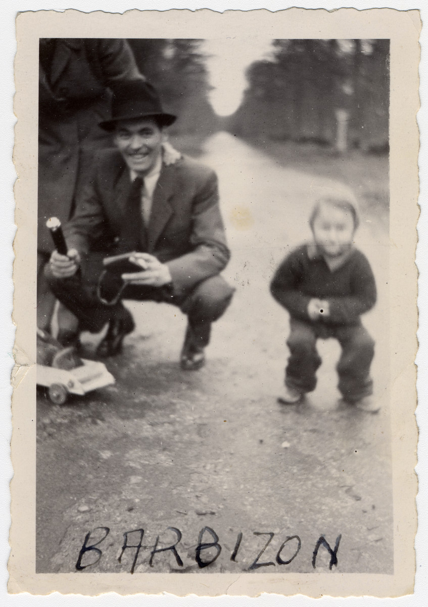 Bela Rosenthal huntches down next to his son Leslie on the grounds of the Barbizon children's home near Paris.