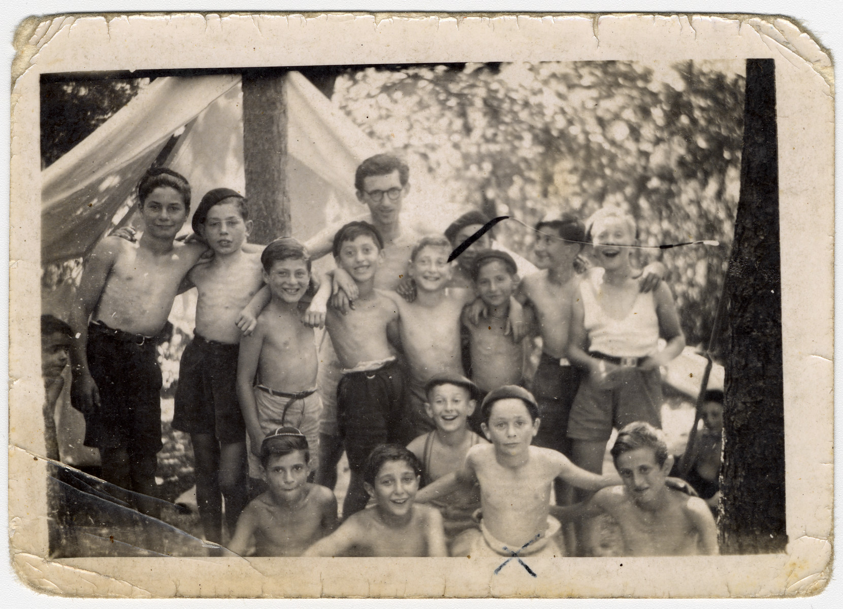 Group portrait of children from the Chateau des Morelles next to a tent in the woods.  Markus Horowitz is pictured in the front row, second from the right.  Henri Dybris, a teacher, is standing in the back, center.