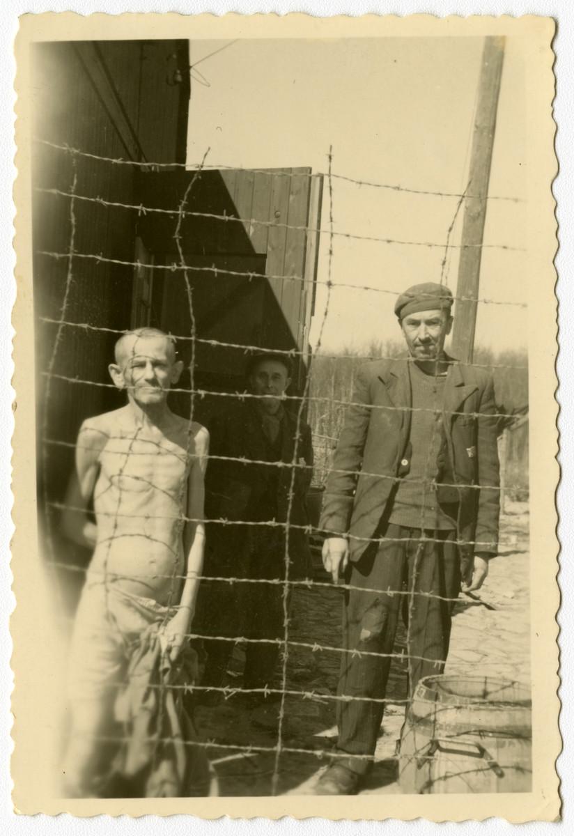 Survivors stand behind a barbed wire fence in Buchenwald.