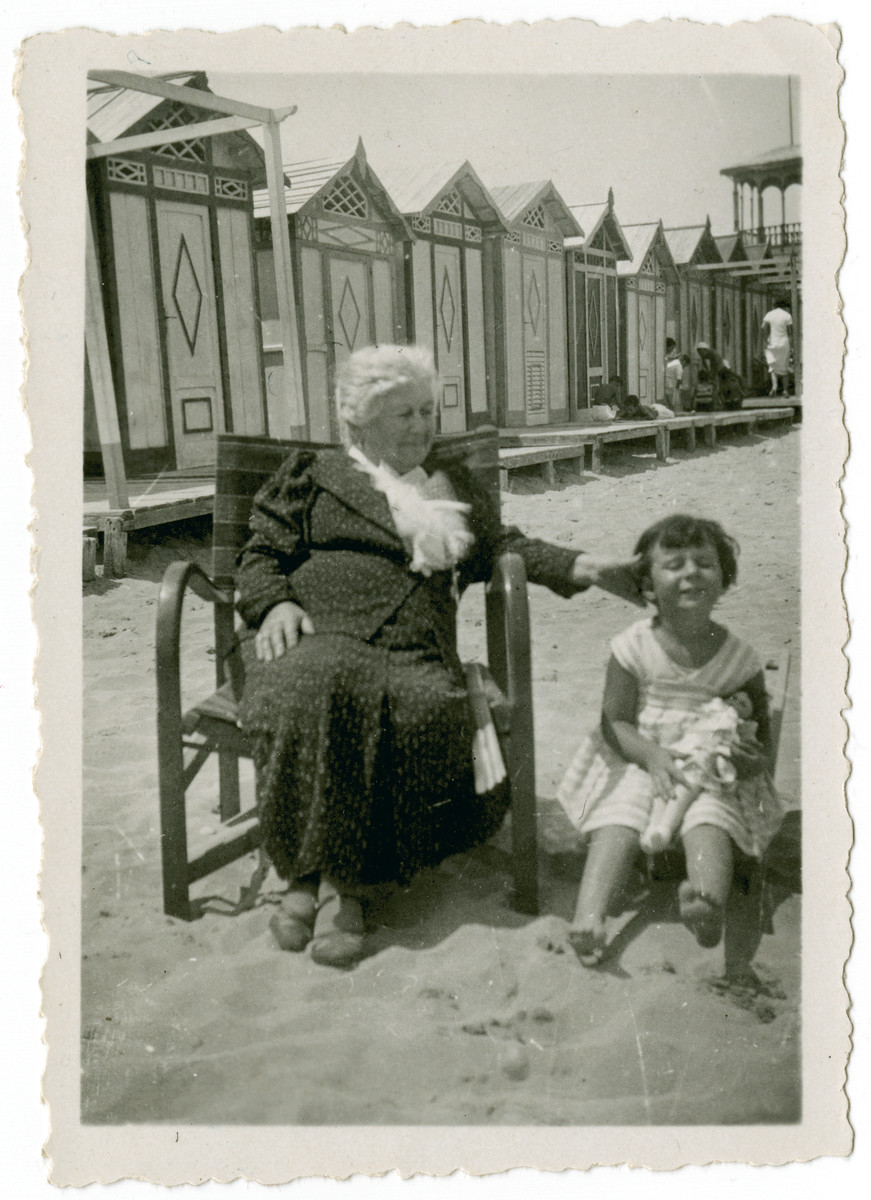Clotilde Coen Nacamu rests on the  Ancona beach with her granddaughter Paola Ducly.