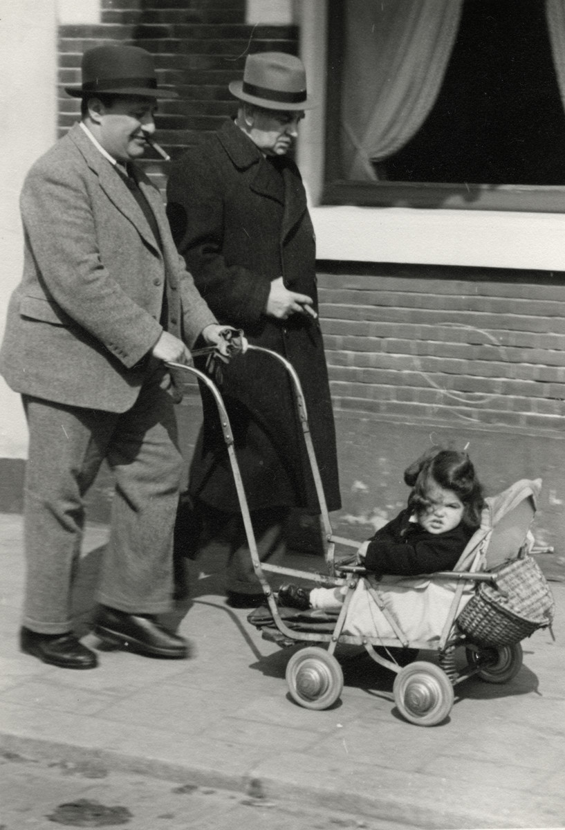 Felix Tikotin pushes his daughter Leentje in a baby carriage down a street in The Hague either right before or right after the German invasion of The Netherlands.
