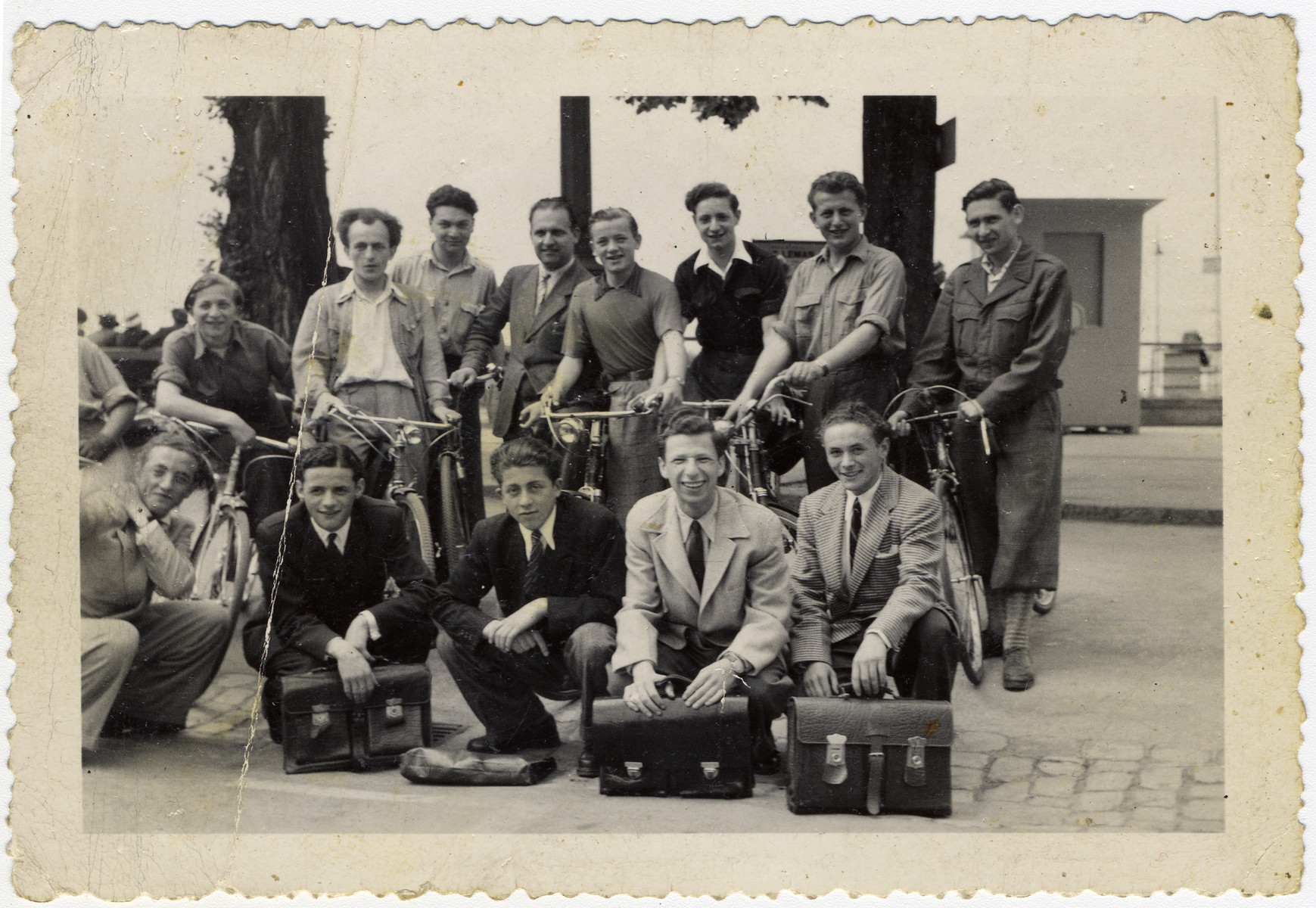 Group portrait of Jewish youth, some with briefcases, others on bicycles, in Geneva.  Among those pictured in the front row is Murray (Monek) Goldfinger and behind him is Henry Kolber.