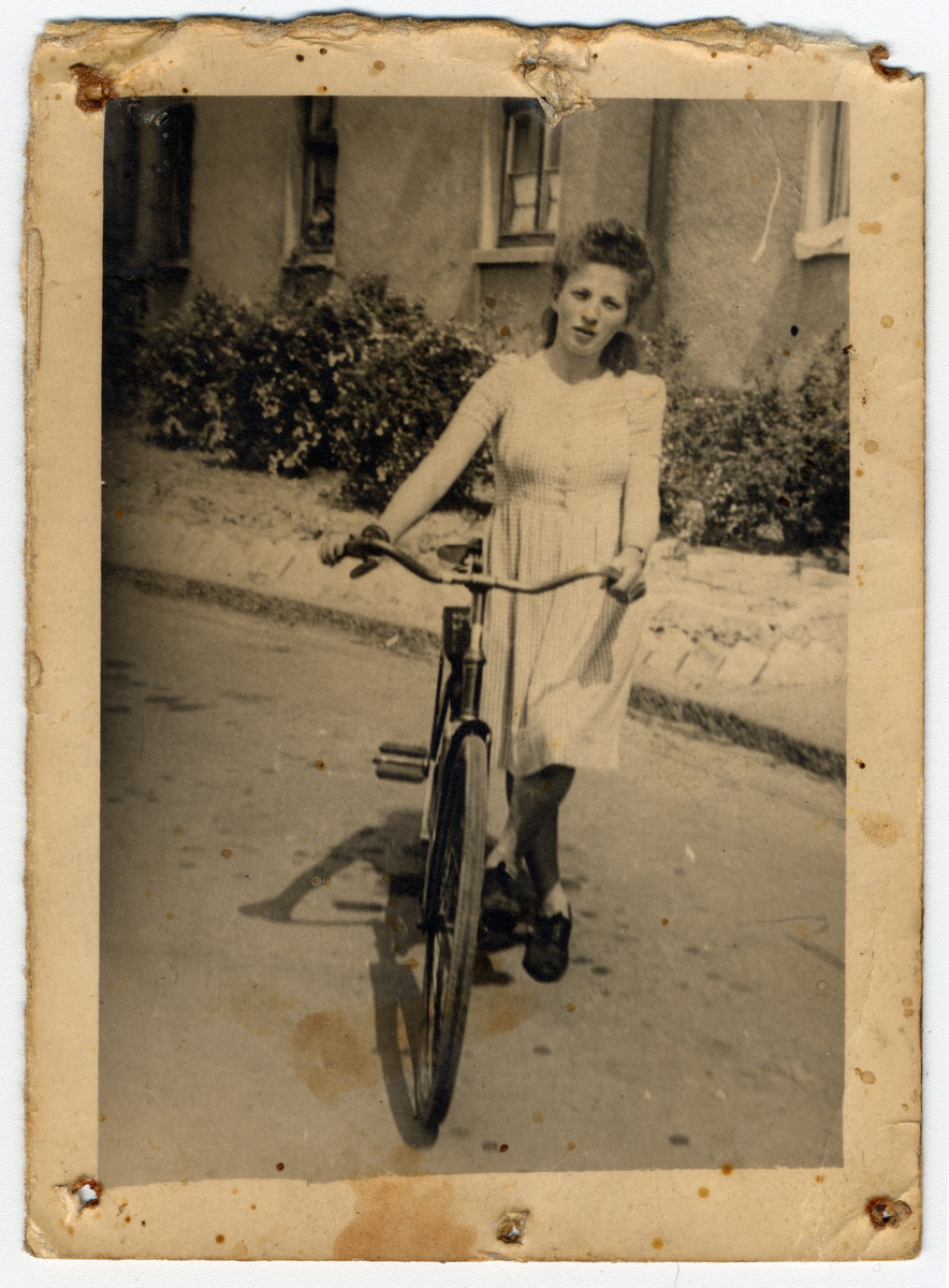 Lili (Frydman) Frankel poses with her bicycle in the Bergen-Belsen displaced persons' camp.  She is wearing a dress purchased for her by her roommate at the camp, who had a job.  It was the first dress she had worn as an adult.