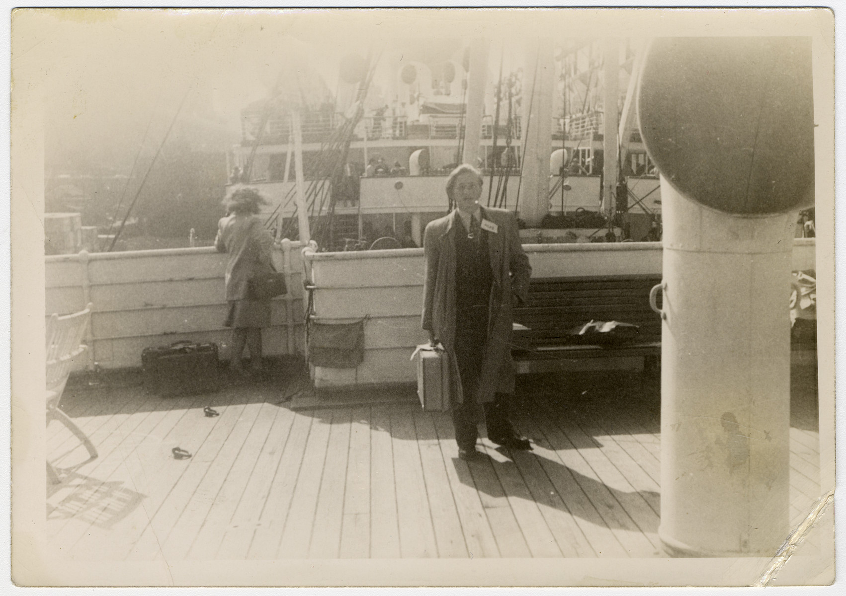 Henry Kolber stands on the deck of a ship holding his suitcase while en route to America.