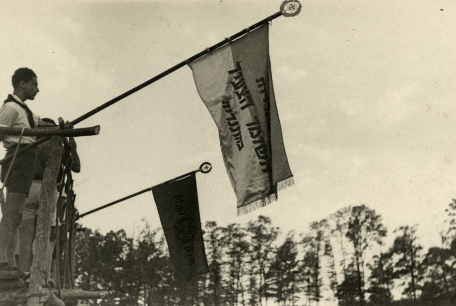 Ephraim Teichman holds the Shomer Hatzair flag in Shomria, a Zionist summer camp in postwar Hungary.