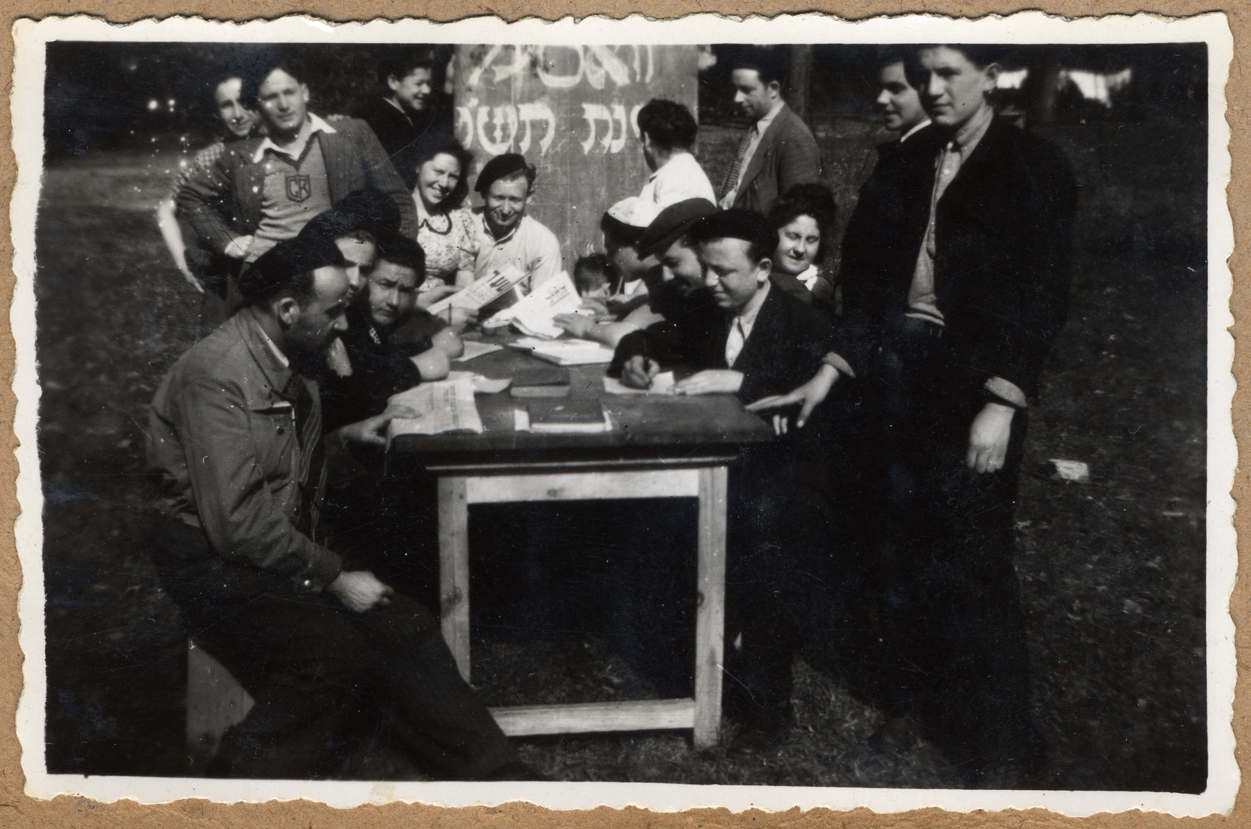A group of teenage boys who were liberated from Buchenwald gather outside by a table to share information and read.    The sign in the background ireferences the Hebrew New Year 5706 which fell on September 8, 1945.