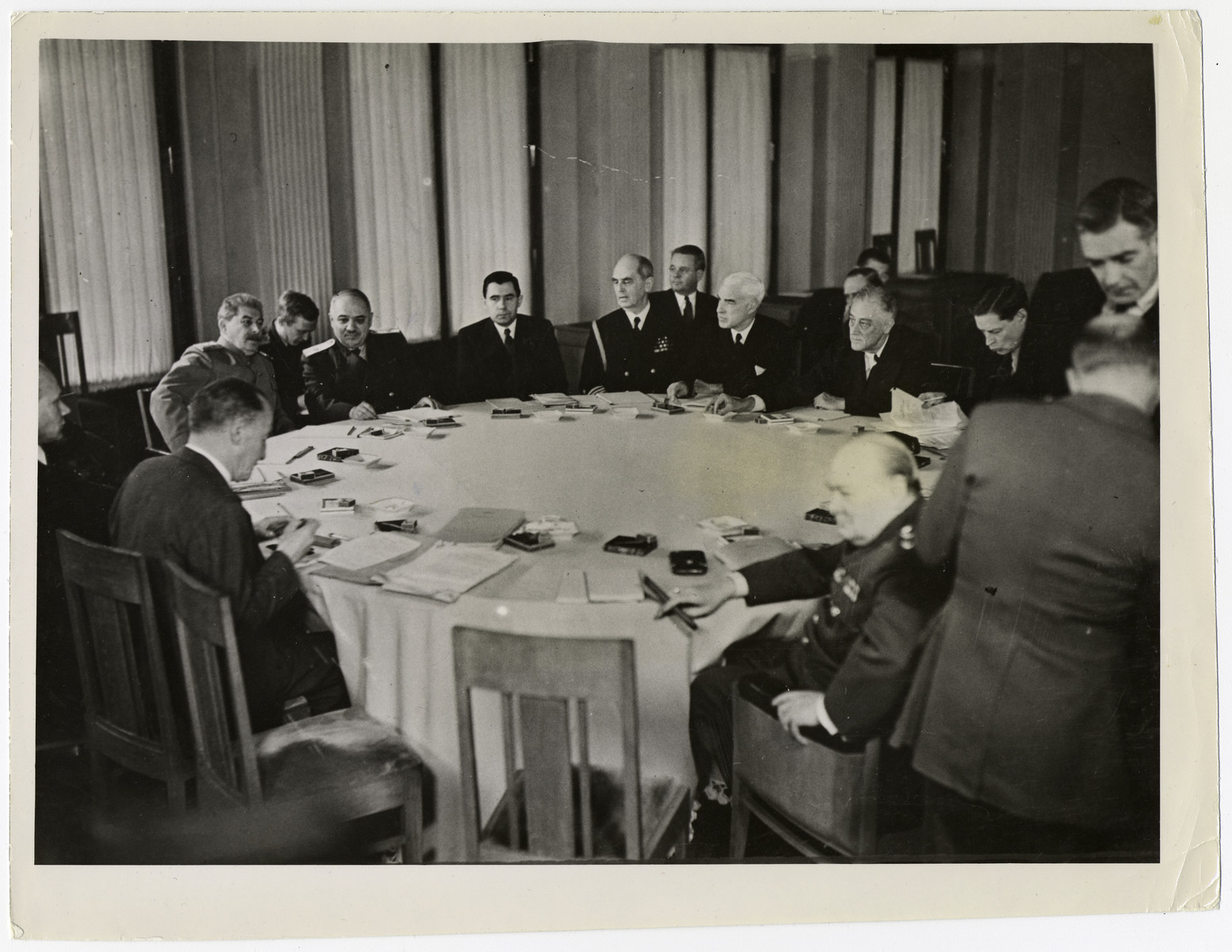"The three Allied powers sit around a conference table in negotiation during the Yalta conference.  The original caption reads:   ""THE CRIMEA CONFERENCE Soviet Marshal Josef V. Stalin (far left), U.S. President Franklin D. Roosevelt (right) and British Prime Minister Winston S. Churchill (foreground) are shown in a general view of the conference table during a meeting of the three Allied powers in February, 1945, at Yalta, Crimea.  U.S. Signal Corps"""
