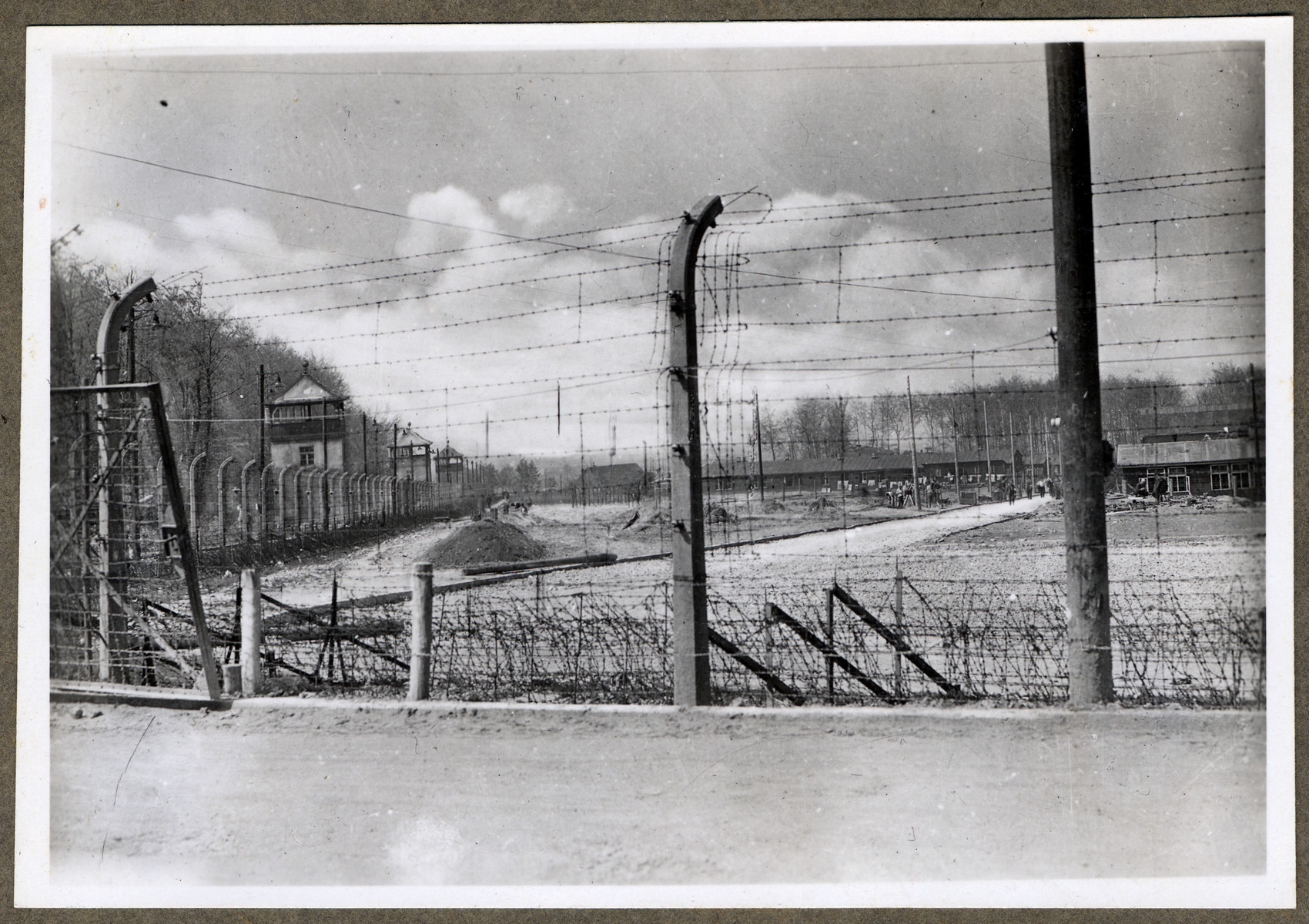View of a section of the barbed wire fence and row of watch towers that surround the Buchenwald concentration camp.