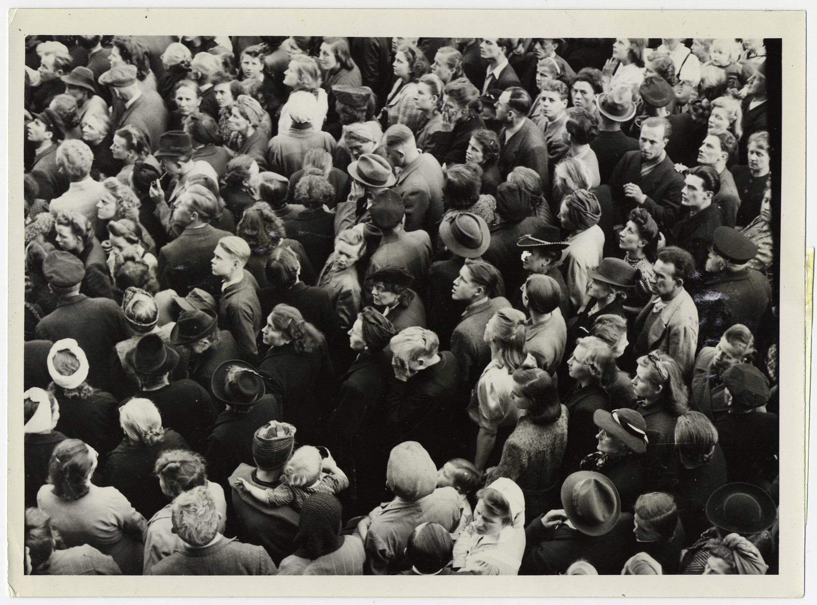 "Official British photograph showing German civilians listening to the terms of German surrender.   Original caption reads: ""Thousands of German civilians gathered in the square in front ot the ancient Town Hall at Lueneburg to hear the official news of the surrender of all the German armed forces in Europe. A British loud speaker van was used to relay the news in German.  An old woman in centre of crowded square weeps as she hears the news."""