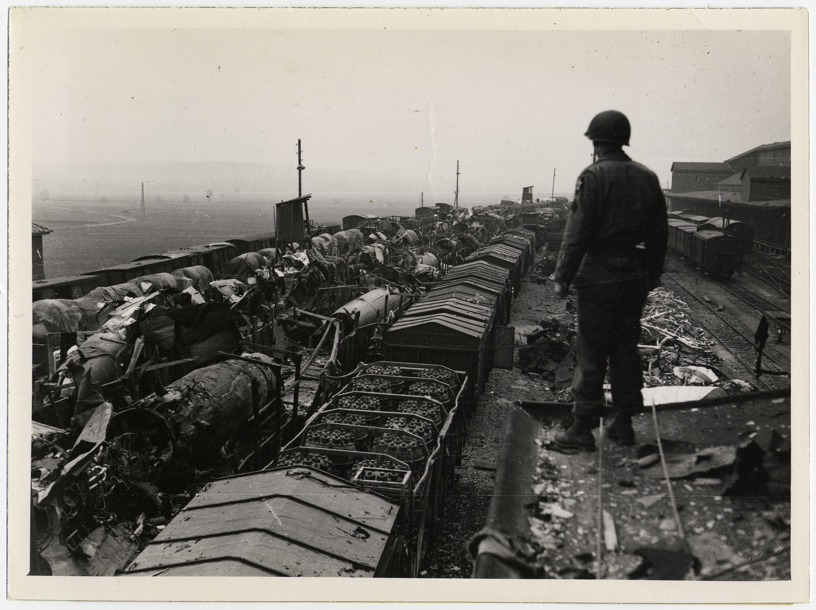 """An American soldier inspects rail cars filled with wrecked V-2s which were brought from the underground factory to nearby Kleinbodugen. Before evacuating  in the path of the First U.S Army advance, Nazi officials removed and destroyed as machinery as possible.  [original caption]  Original caption reads: """"Nazi weapons of death made by dying slaves is the grim story of Nordhausen , Reich center for V-bomb production which was captured by troops of the First U. S. Army April 10, 1945. Hundreds of dead and dying lay in the same beds in a nearby slave camp where, according to the liberated, 9,000 lost their lives in 1944. The American officer in charge immediately ordered the leading citizens of Nordhausen to bury the rotting and skeleton-like dead, choosing a burial site on a hillside overlooking the V-bomb factory where the slave workers had been already murdered. The factory, assembly plants for V-1 and V-2 weapons , was a series of deep underground tunnels. Three main tunnels were connected with 42 smaller ones. Until May, 1944, workers were never allowed outside. When the slaves, who labored  in 18-hour shifts, became too weak to work, they were loaded into box cars and never seen again."""""""