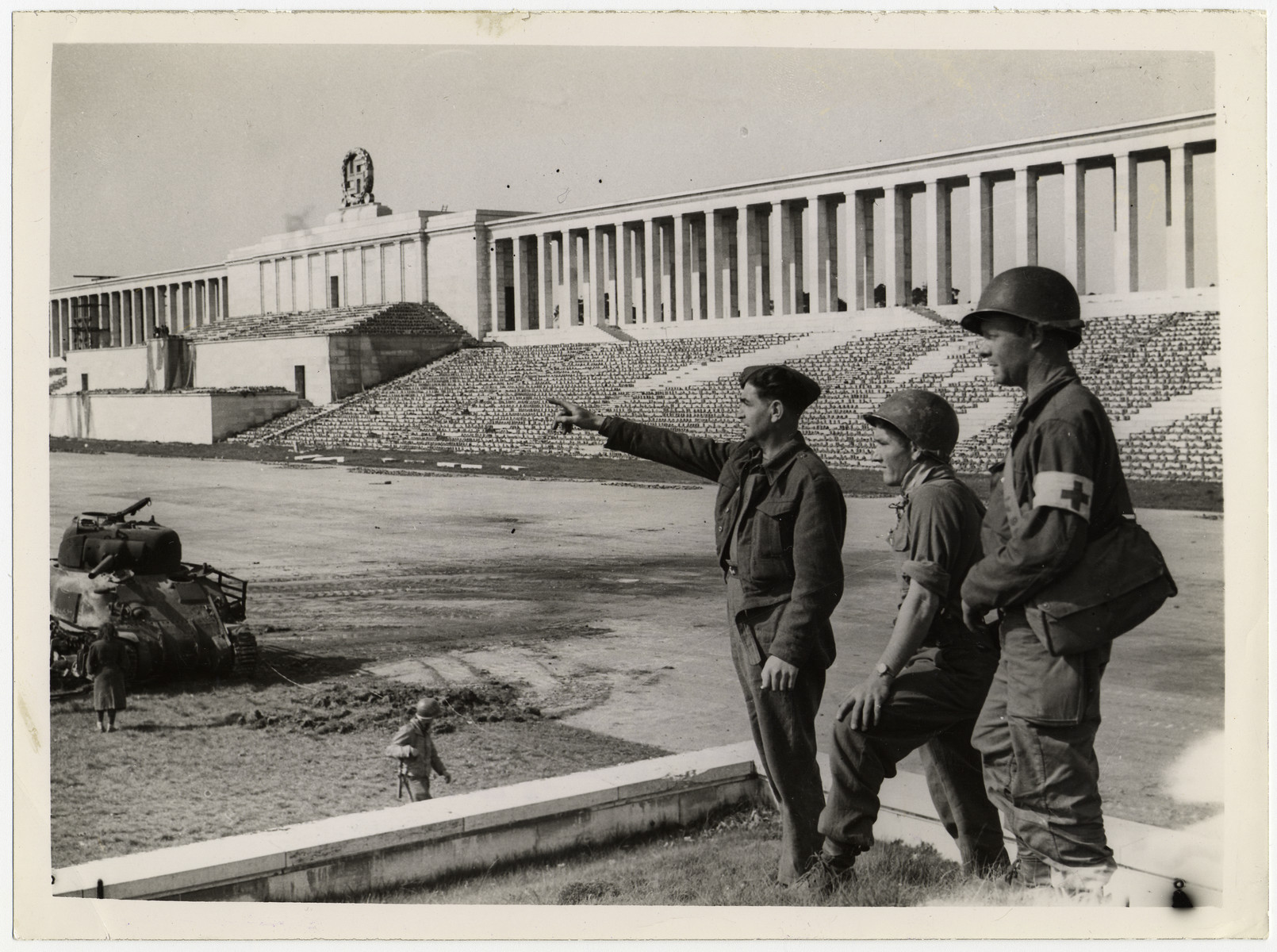 """A liberated British prisoner-of-war shows the Nuremberg stadium to two American soldiers.  Original caption reads:  """"LIBERATED BRITISH PRISONER SHOWS NUREMBERG SIGHTS TO YANKS FROM HITLER'S STADIUM. Captured at Dunkirk 5 years ago, a British soldier now liberated points out landmarks of Nuremberg from the Egpelin Stadium to Pte Dewey Serrogins of Sataria, Miss.Abd Pte William Layton 1111 Red Bud Ave. St Lois, Miss. (left to right) The stadium was used for great Nazi part rallies and Hitler often spoke from the Rostrum seen in the picture."""""""