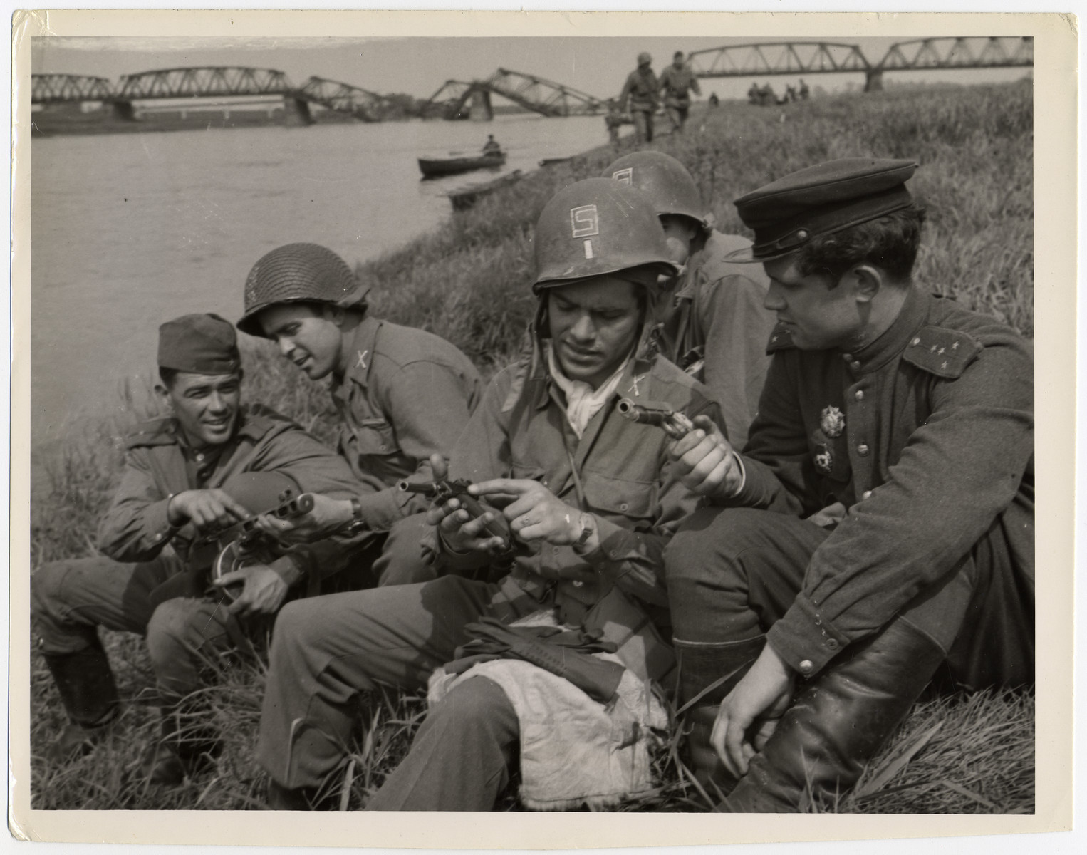 "Soviet and American soldiers show each other their pistols while relaxing on the banks of the Elbe River.  Original caption reads: ""U.S AND RUSSIAN FORCES LINK UP A linkup between the First U.S. Army and the Russian First Ukrainian Army was made on the Elbe River at the town of Torgau, approximately 60 miles south of Berlin, at 4:30 P.M. April 25, 1945. The historic joining was effected by patrols of the 273rd Infantry Regiment of the 69th Division of General Courtney Hodges' First U.S. Army and infantrymen of the 173rd Regiment of the 58th Guards Division of Marshal Ivan Stopanovich Koniev's First Ukrainian Army. A U.S. patrol of four men and met Russian infantrymen and brought back four Russian officers to 69th Division headquarters. The following day, April 26, formal meetings were held between the high Soviet and U.S. officers near the Elbe at Tergau. To facilitate the linkup and to clearly mark the area held by the First U.S. Army., General Hodges' troops advanced to the line of the Huldo River, where they awaited the Red Army forces. The choice of such an easily recognized natural feature eliminated the chances of tragic cases of mistaken identity by either of the allies.  THIS PHOTO SHOWS; Russian and American soldiers examine each other's weapons following the historic linkup. From left to right: Thomas Federovitch Alexander Paualov of Newgrad, Ukraine: Lieutenant Ralph Phillips of Union, South Carolina; Lieutenant Dwight Brooks of Los Angeles, California, and Captain Michael Organez of Dubnel. In the foreground, the blasted bridge over the Elbe may be seen. CWI Staff Photo by George Greb."""