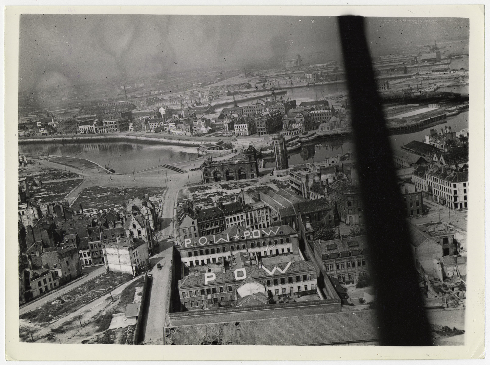 "British official aerial photograph of Dunkirk.  Original caption reads: ""An R.A.F official photographer flew over Dunkirk on 11.5.45 and took these air views of one of the last of the surrendering German outposts. Picture shows:- General view over the town of Dunkirk showing prisoner of war signs painted on the roofs of buildings."""