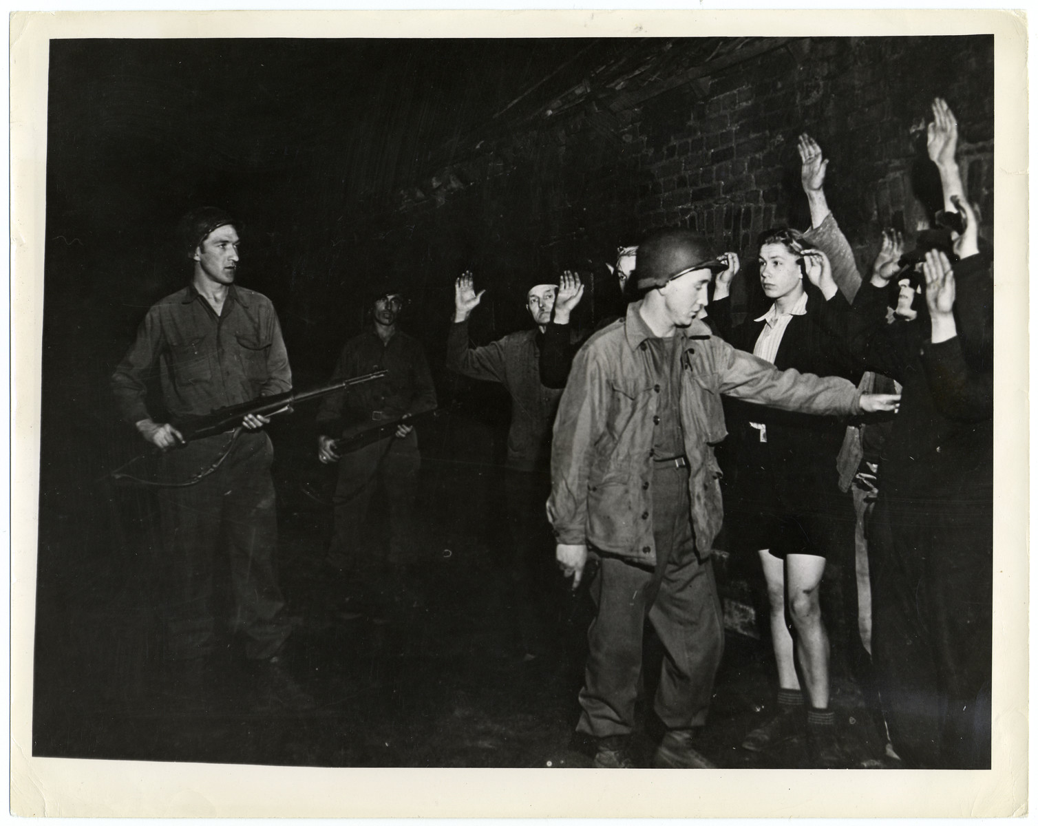 Sergeant Paul Campbell (foreground) of Johnstown, Pennsylvania, accompanied by two infantrymen, searches lined-up civilians in Recklinghausen, Germany for concealed weapons April, 26,1945.   They are looking for a Nazi sniper who fired on a Ninth U.S Army soldier. Recklinghausen, a Ruhr town 23 miles northeast of Duisburg, was captured April 3. [original caption]