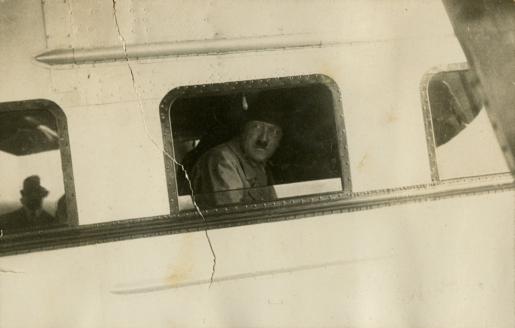"View of Adolf Hitler from his personal airplane, at airport in Bremen, Germany, 1932.   Original caption on album page reads, ""Hitler. Germany 1932."" Photo-specific caption reads, ""Hitler in his own plane."""