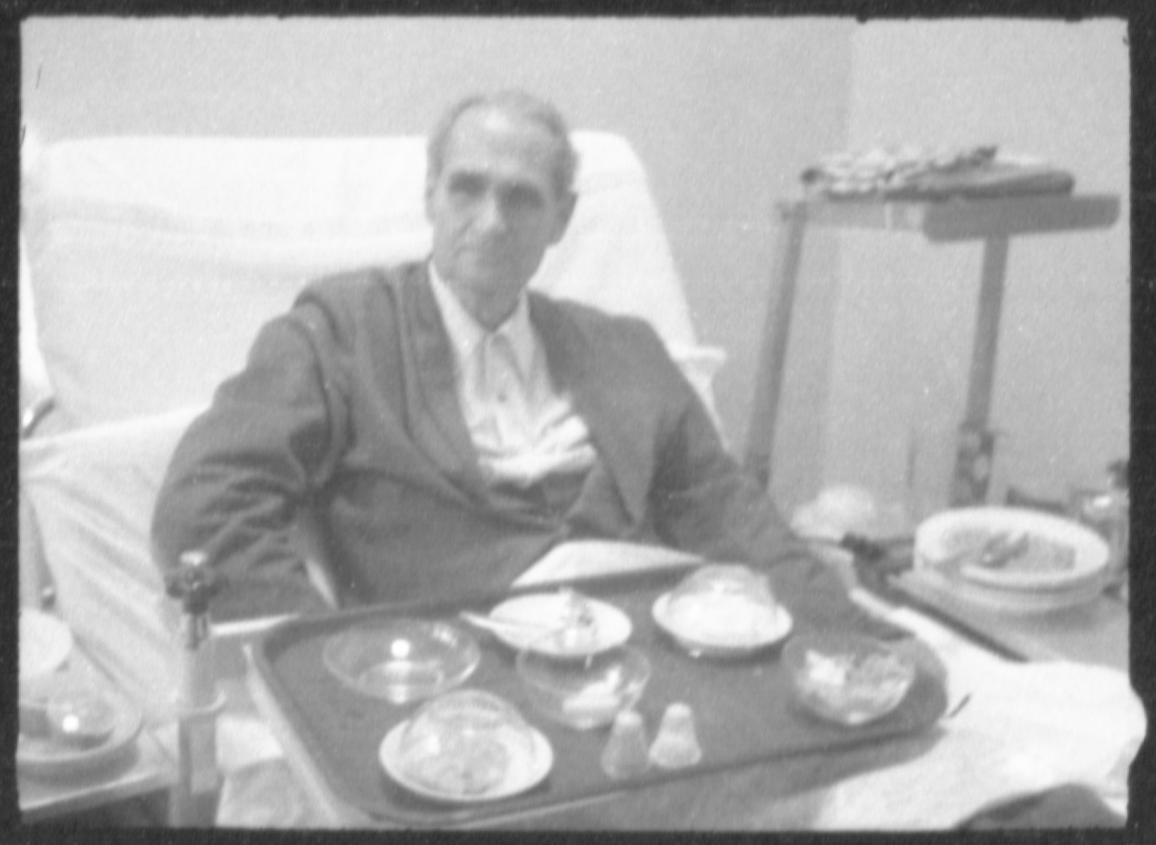 Clandestine photographs of Rudolf Hess sitting in his hospital bed with his tray of food in the Spandau Prison.