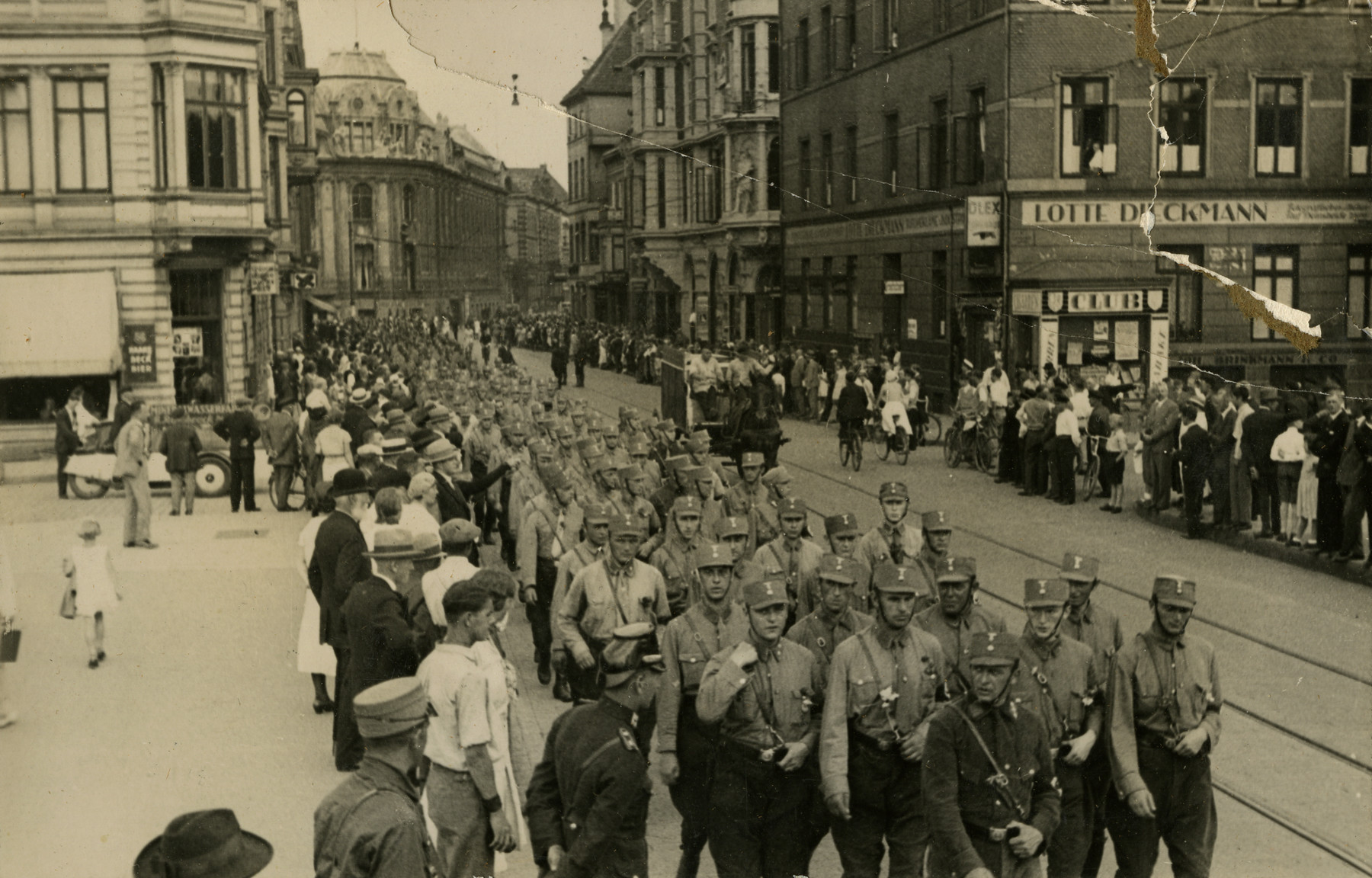 "Street view of Nazi soldiers marching through the streets of Bremen, Germany in 1932.  Original caption on album page reads, ""1932 Germany."" Bottom-most photo caption reads, ""A gathering of Hitler supporters in Hamburg before election in 1932."" Top photo caption reads ""Hitler Soldiers marching the street at Bremen; Irving and I saw their parade."""