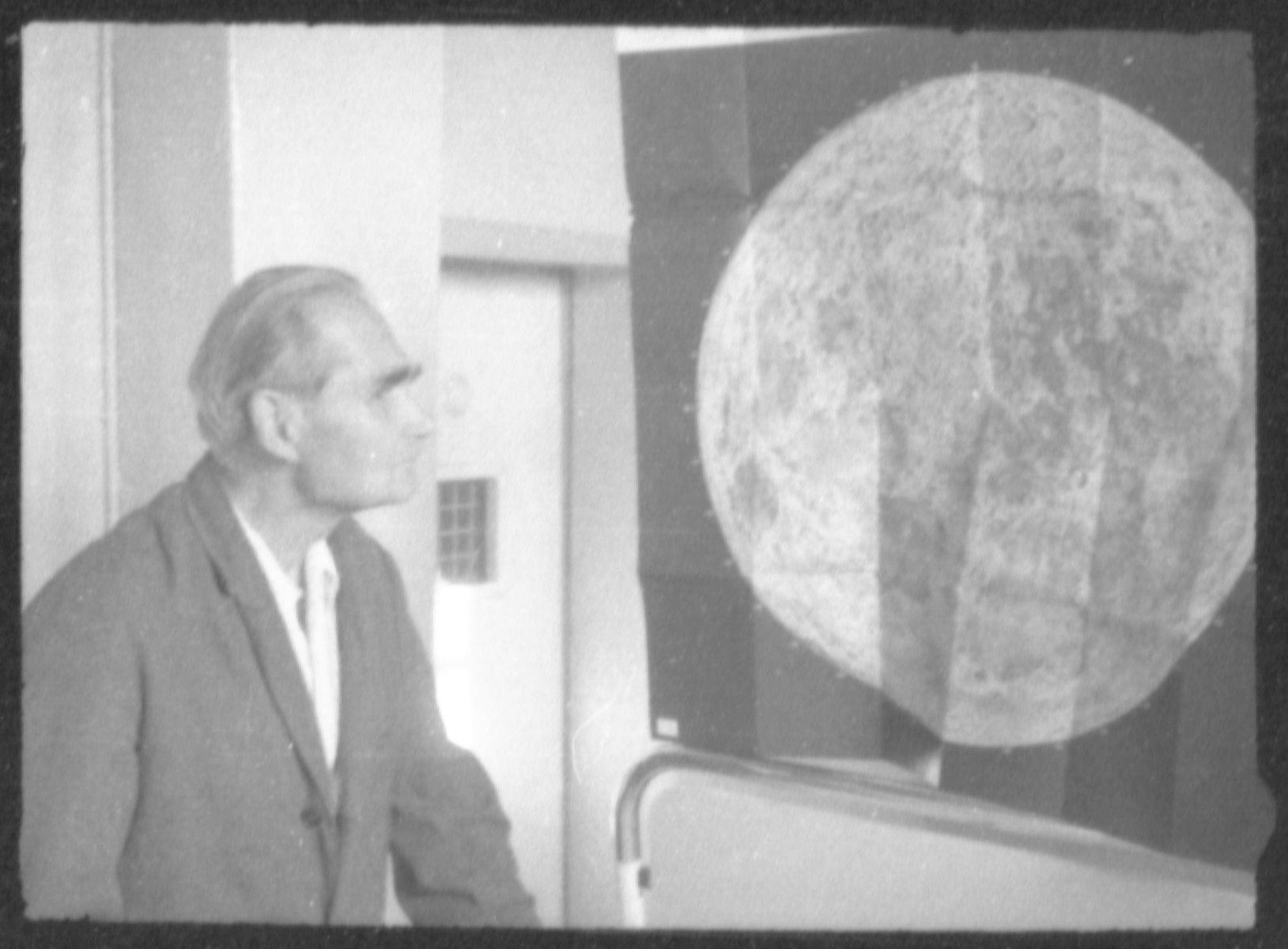 Rudolf Hess studies a poster of the moon in Spandau prison.