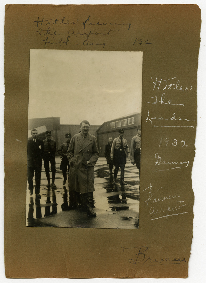 """Album page with photograph of Adolf Hitler leaving the airport in Bremen, Germany, 1932.  Original caption on album page reads, """"Hitler leaving the airport field, Aug. 1932."""" A secondary caption reads, """"Hitler the leader. 1932, Germany. Bremen Airport."""""""