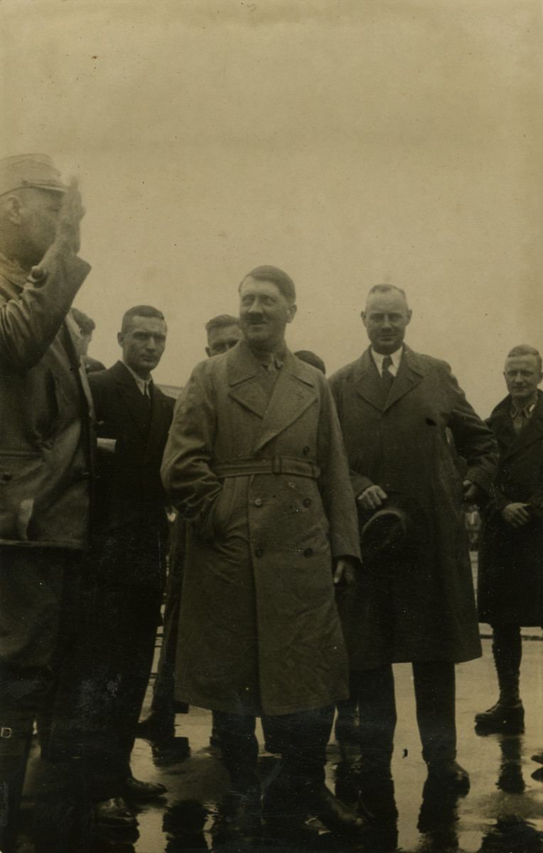 "Adolf Hitler poses with comrades in Bremen, Germany.   Original caption on album page reads, ""Adolf Hitler being saluted by comrade. Aug. 1932, Bremen, Germany."""