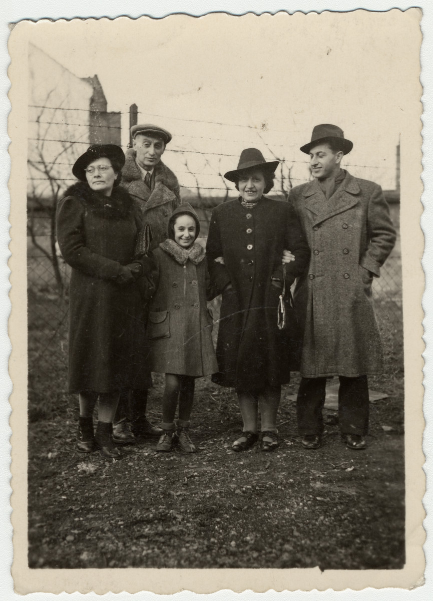 Members of the Engel family stand by a fence on their after the war.  Pictured are Greta Stoessler Engel, Ludwig Engel, Katie Engel, Marta Mandler (a cousin of Greta) and Victor Adler (b. 1929; a cousin of Katie).