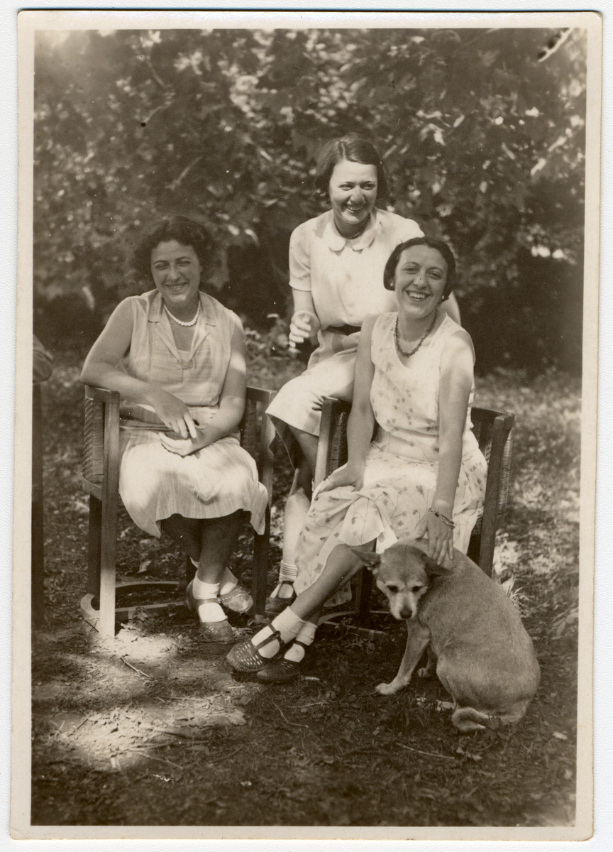 Three Austrian-Jewish sisters sit in a garden with their dog.  Pictured are Stella, Greta and Erna Stoessler.