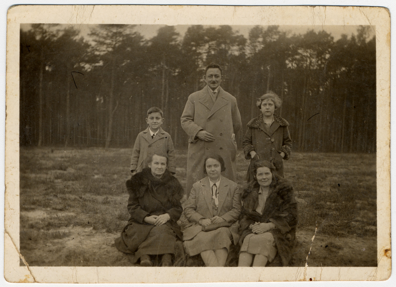 Standing from left to right are Hans, Max, and Ilse Hanauer.  Below them (from left to right) sit Marie Teske, Frieda Hanauer, and an unknown woman.  The family is posing in front of a forest.