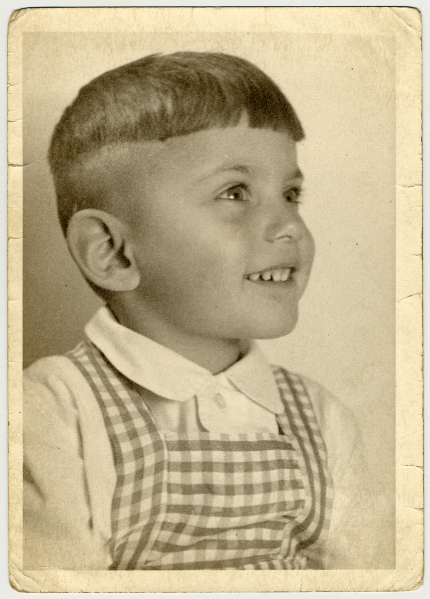 Studio portrait of a young boy in a plaid jumper.  Pictured is Uri Hanauer, a year before his deportation to Theresienstadt.
