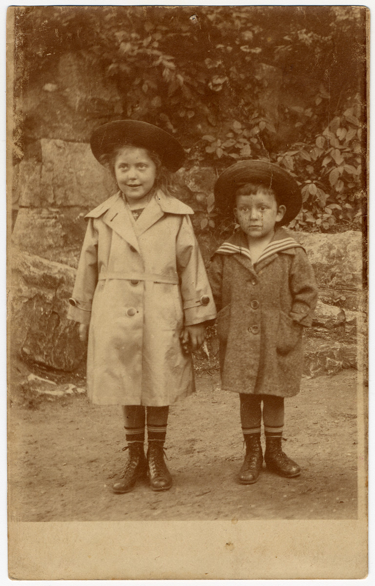 The young siblings, Ilse and Hans Heinz Hanauer, hold hands outside in their trench coats and hats.