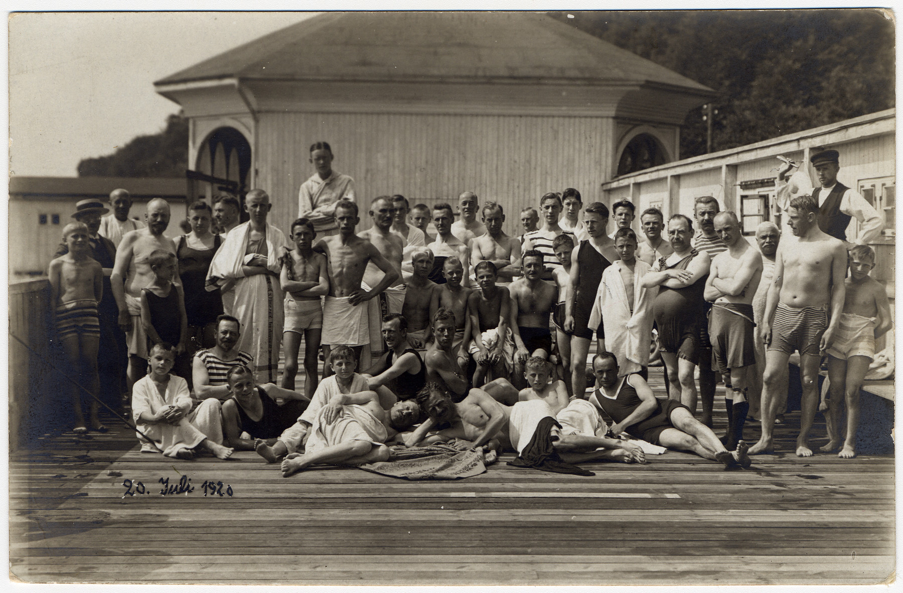 Max Hanauer sits in the center wearing black swimming trunks.