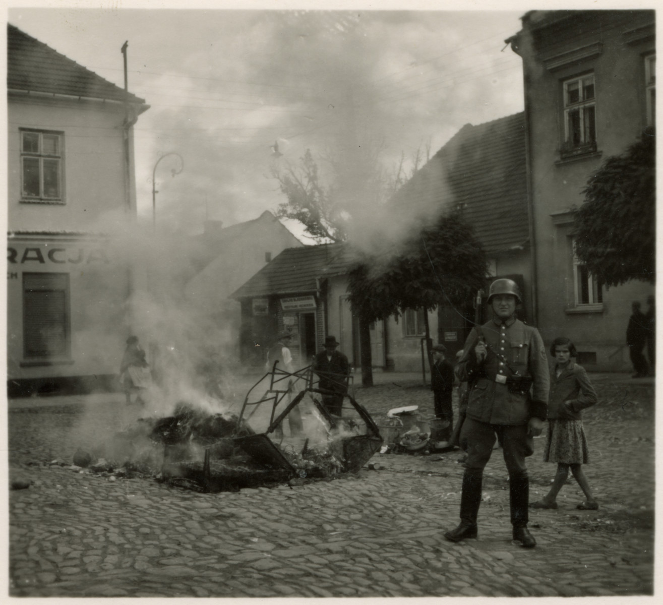 "Propaganda photo showing a German soldier guarding a bonfire of burning mattresses.  The original caption reads: ""Roach and lice-ridden Jewish beds being burned in the market square in Myslenice.""  The photograph was part of a series of stereographic prints depicting the occupation of Poland entitled ""Die Soldaten des Fuehrers im Felde.""  (The Fuhrer's soldiers in the field.  The photographs were mass produced and published by Raumbild-Verlag-Otto Schönstein."