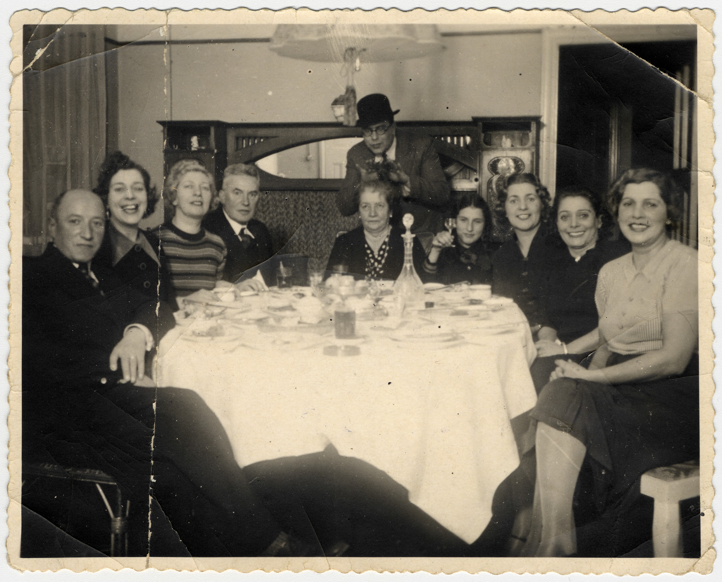 A Latvian-Jewish family gathers around its dining room table.  The photo was taken in the home of the donor's aunt, Gusti Jakobson Akermann.  Left to right: Oskar (Gusti's husband), Lena and Rita Jakobson (sisters of Klara and Gusti), Marta Schiftan (the mother-in-law of Tania Jakobson Schiftan), Luba Akermann, Klara Schwab, Hermina Jakobson, and Gusti Akermann.