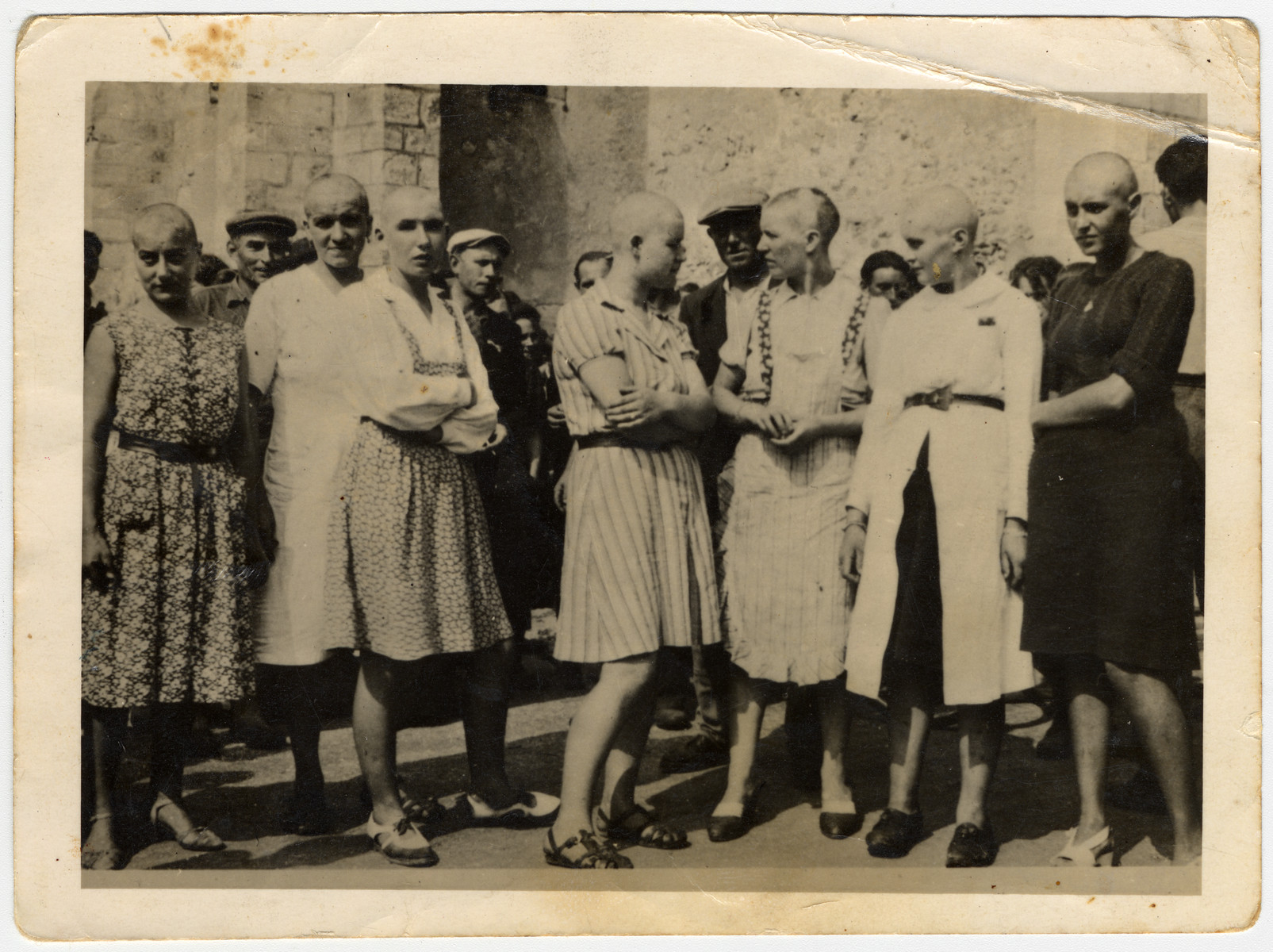 Women accused of collaborating with the Nazis are publicly humiliated by having their heads forcibly shaved after the war in either France or Belgium.  Note: Similar displays took place in both France and Belgium and there is no original documentation indicating where this photo was taken.