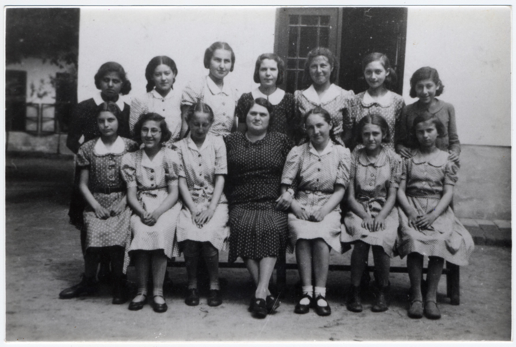 Class photo of the graduating class from the Jewish school of Vac.    Marta Ganzl is seated to the left of the teacher.  Her sister Erna is to the teacher's right.