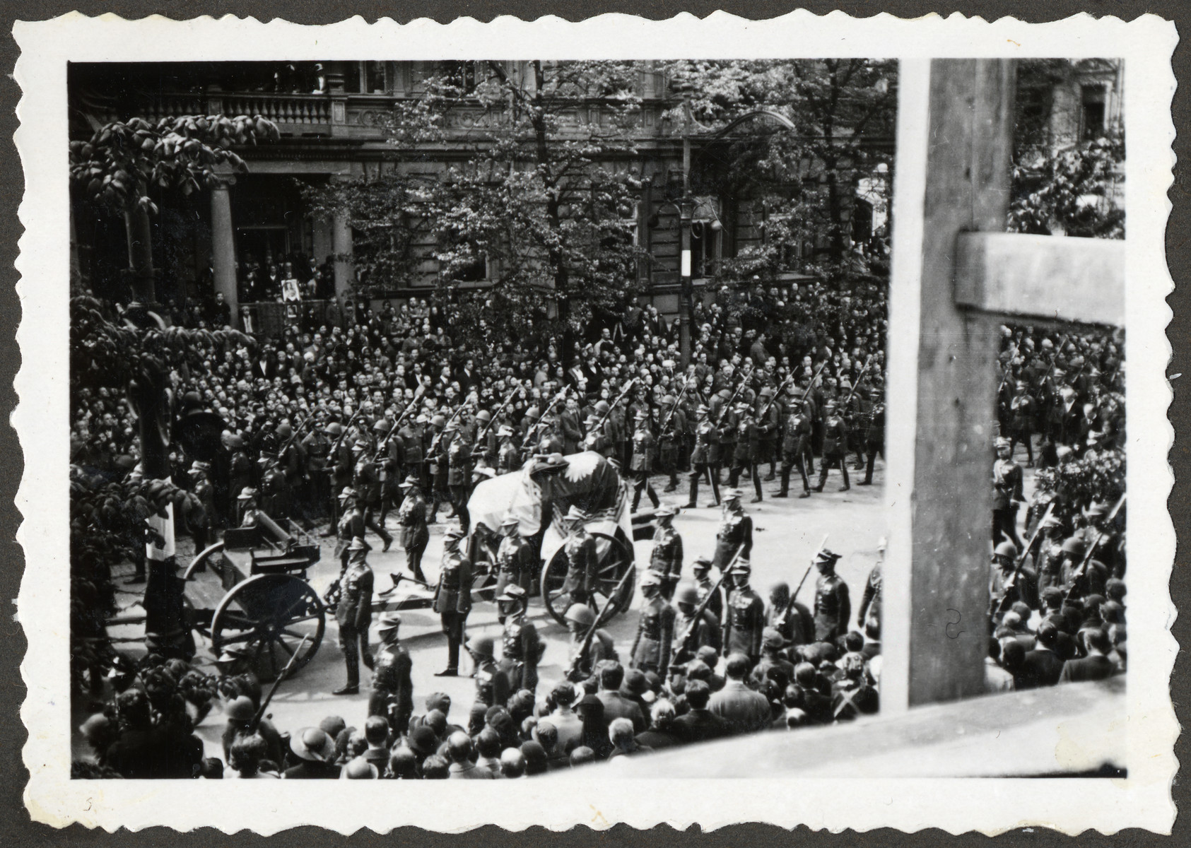 Polish soldiers march down a street in Warsaw escorting the casket during the funeral procession for Marshal Jozef Pilsudski.