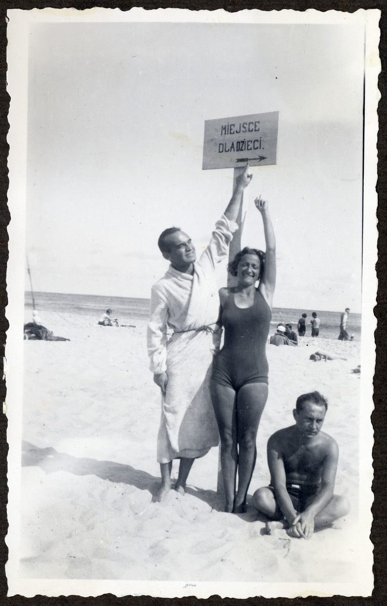 A man and woman hold up a sign reading while vacationing on a beach.