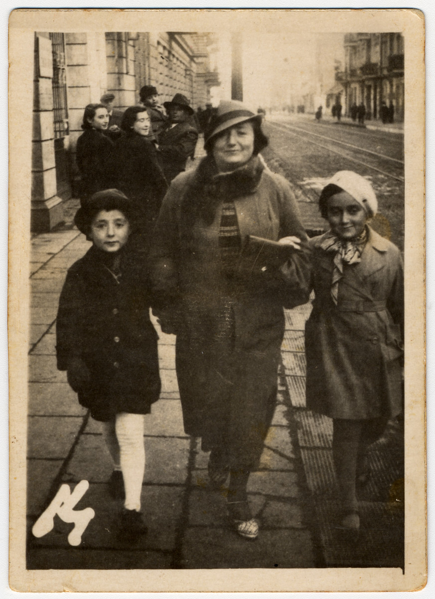 A woman walks down a street in prewar Lodz with her two children.   From left to right are Simon, Hela and Jutta Szmirgeld.