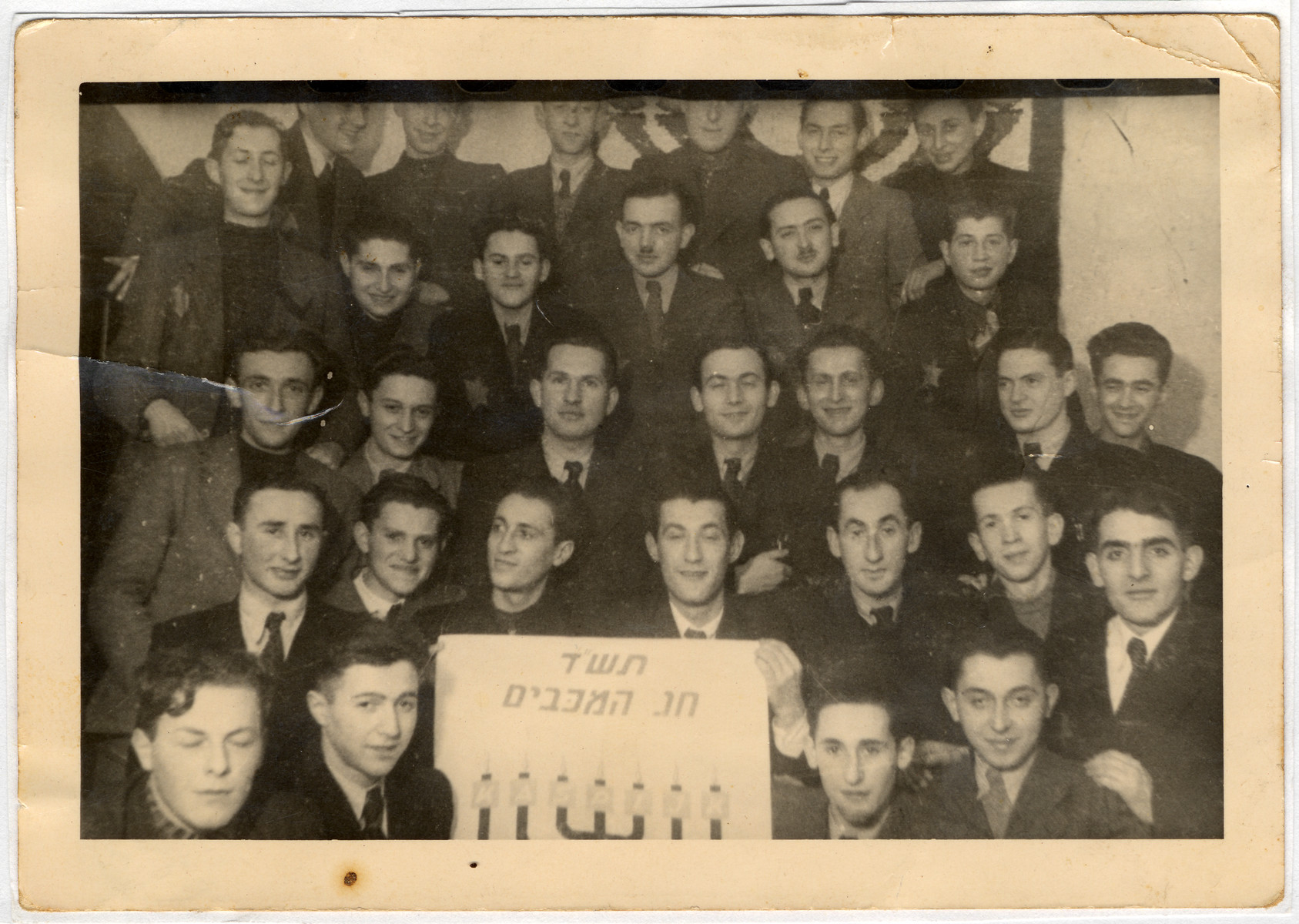 "Members of Hanoar Hatzioni celebrate Chanukka in the Lodz ghetto.    The young men hold a sign with a picture of a menorah that reads,""1943/Festival of the Maccabees.""  The Polish letters on the branches of the menorah spell out the word ""KASPIJK,"" possibly the name of the chapter of the organization.     Standing left to right, first row: Zvi Lautenberg, Przygorski (later Irving Gorsky), Marek Rus and Julian Waks.  Second row: Libicki, Kuba Lubinski, Rozenes, Wiktor Sztajn, Aron Jakubson and Abraham Klugman.  Third row: Josef Waserciser, Alek Szapira, unknown, unknown, unknown, Chaim Rozenowicz and Arie Princ.  Fourth row, Lolek Lubinski, Kliger, Kohen, Adolek Kohen, and unknown.  Top row. Henryk Bergman (far left), others unknown."