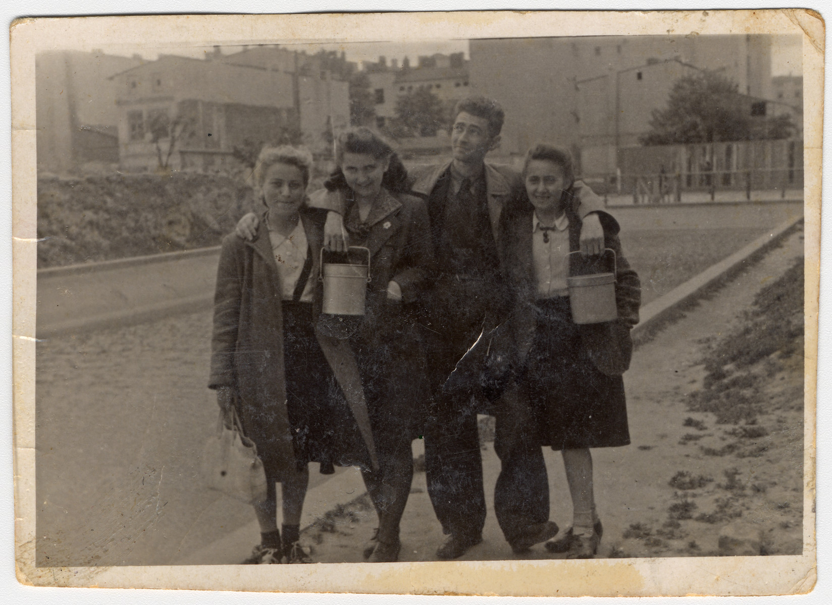 A group of teenagers hold lunch pails in case there will be a distribution of soup while standing in on Marynarska street in the Lodz ghetto.    Pictured from the left are: Rozka Grosman (later Zilbar -- Mendel Grosman's sister), Rachel Beim, Arie Princ (later Ben Menachem) and his fiancee Ewa Bialer.
