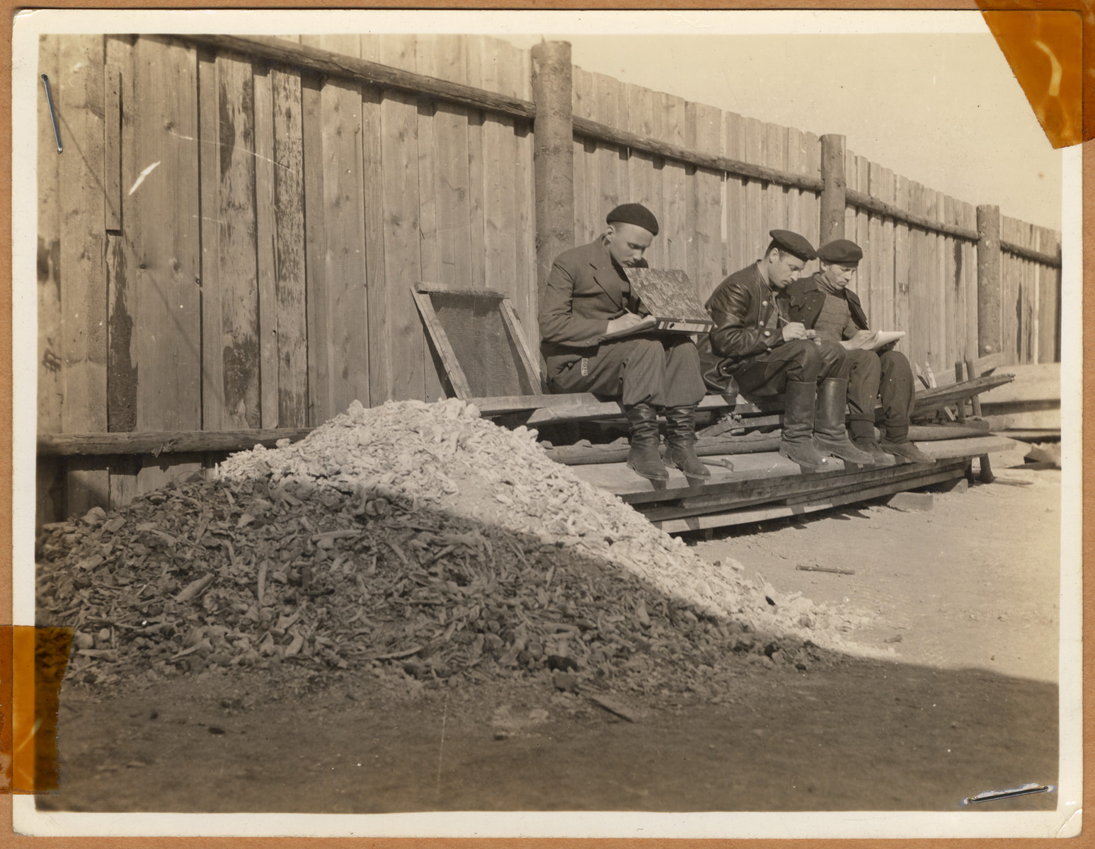 "Survivors sitting next to a pile of human remains shoveled from the crematorium in Buchenwald.  The lender's handwritten caption reads, ""Men writing home, that they are now free.  Beside them, the bones of their comrades. One letter was allowed a month.  Many months the guards would enter the barracks with the mail and say, 'You Swine, you don't need the mail,' then throw it in the fire."""
